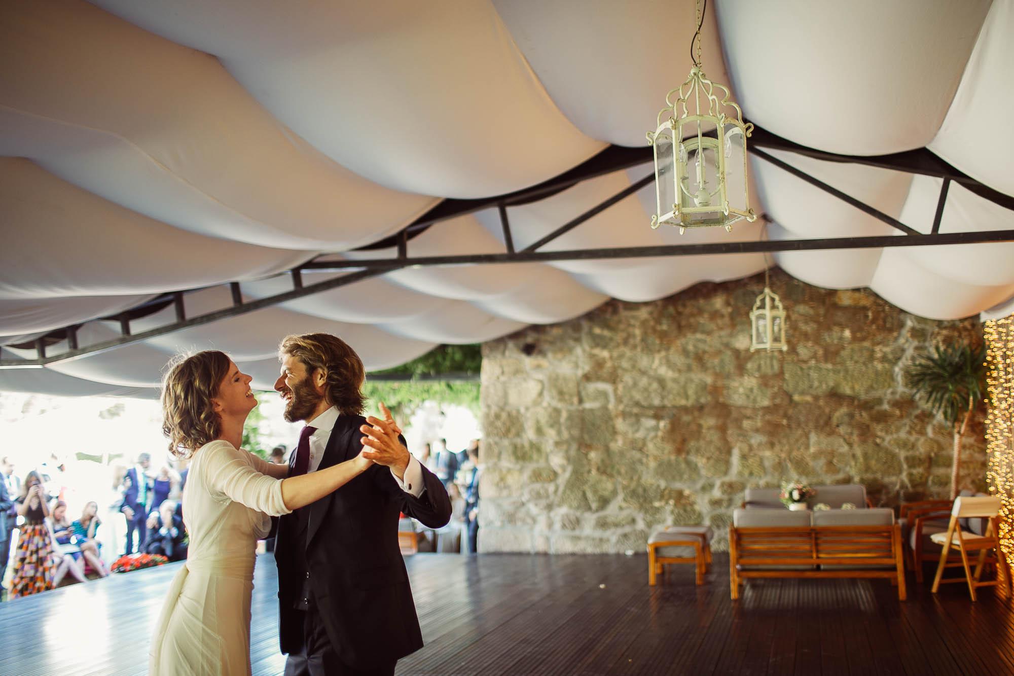Los novios bailando juntos en el salón de baile mientras los invitados los observan y les sacan fotografías