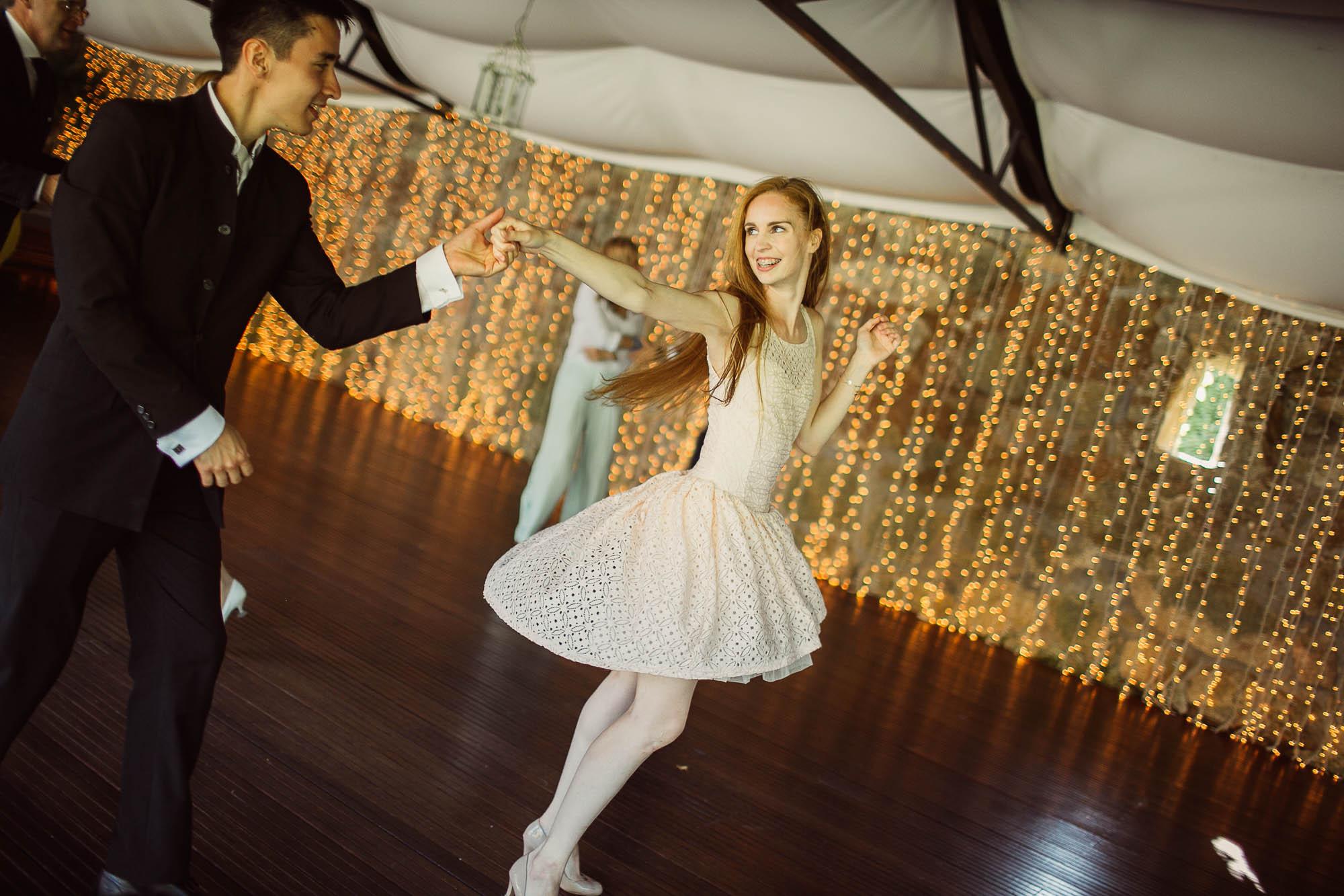 Una invitada con un vestido rosa bailando con otro invitado