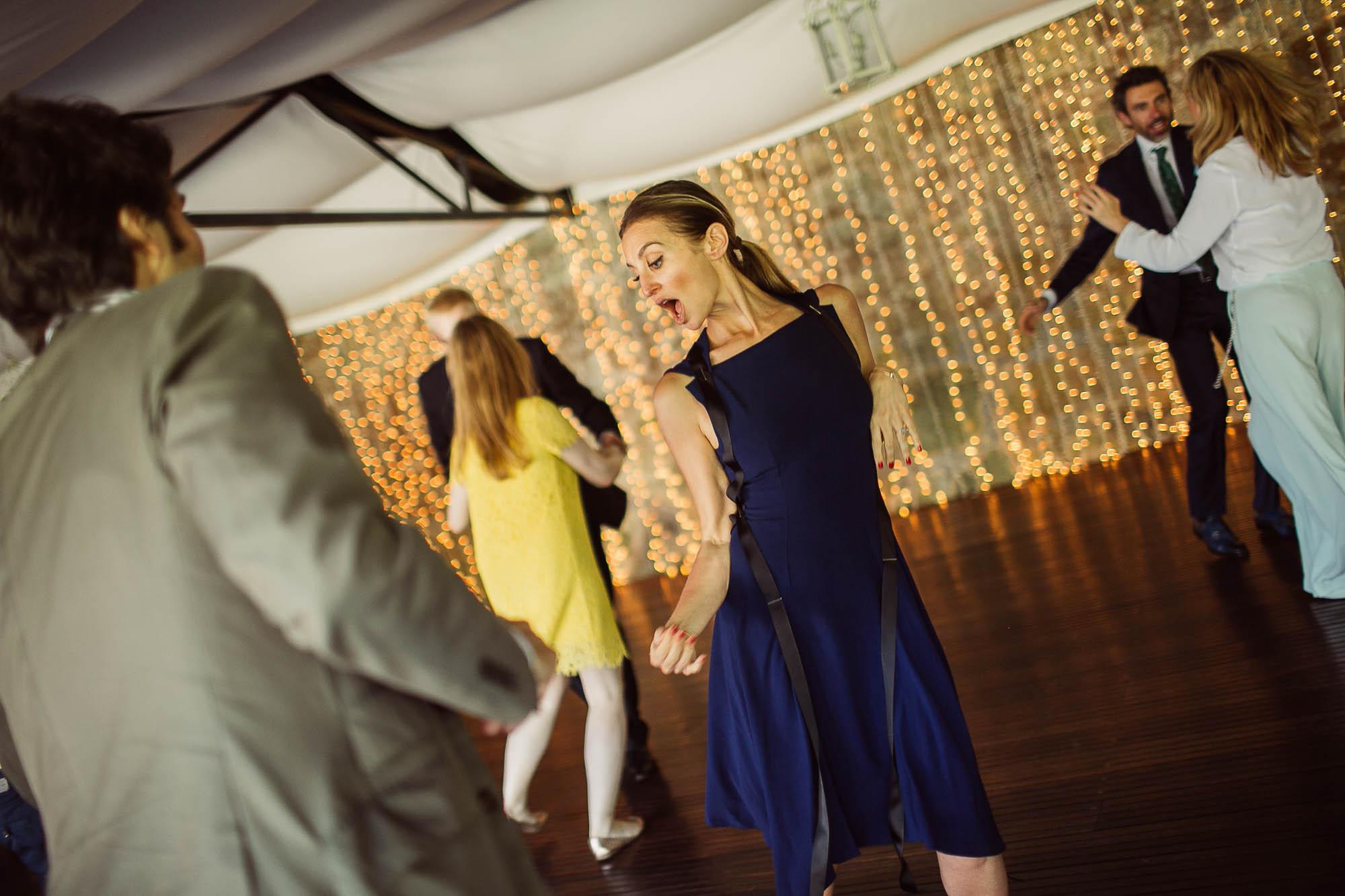 Una invitada con un vestido azul bailando junto a otros invitados