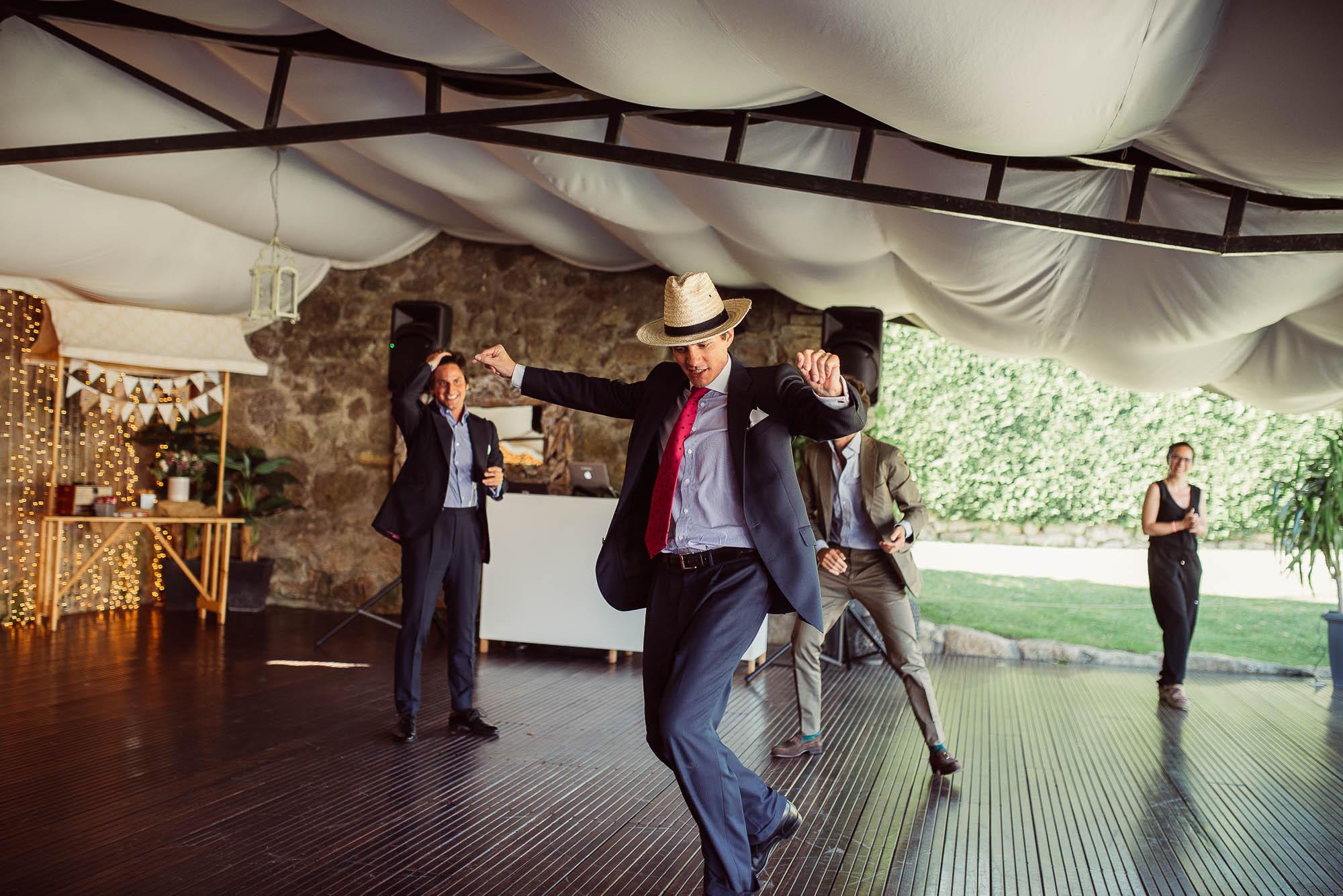 Un invitado con un sombrero de paja deslizándose por la pista de baile