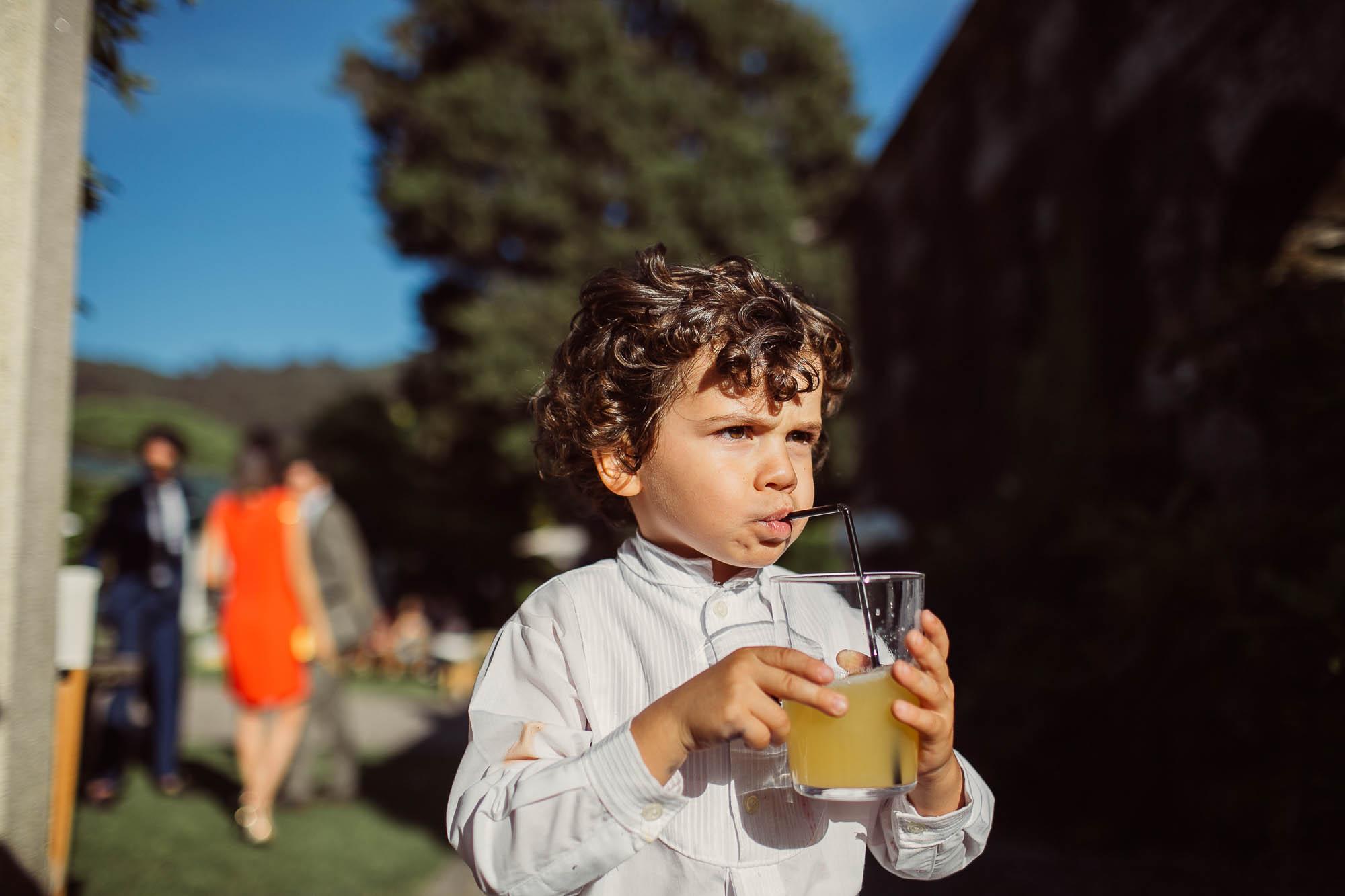Uno niño con un vaso de zumo bebiendo con una cañita