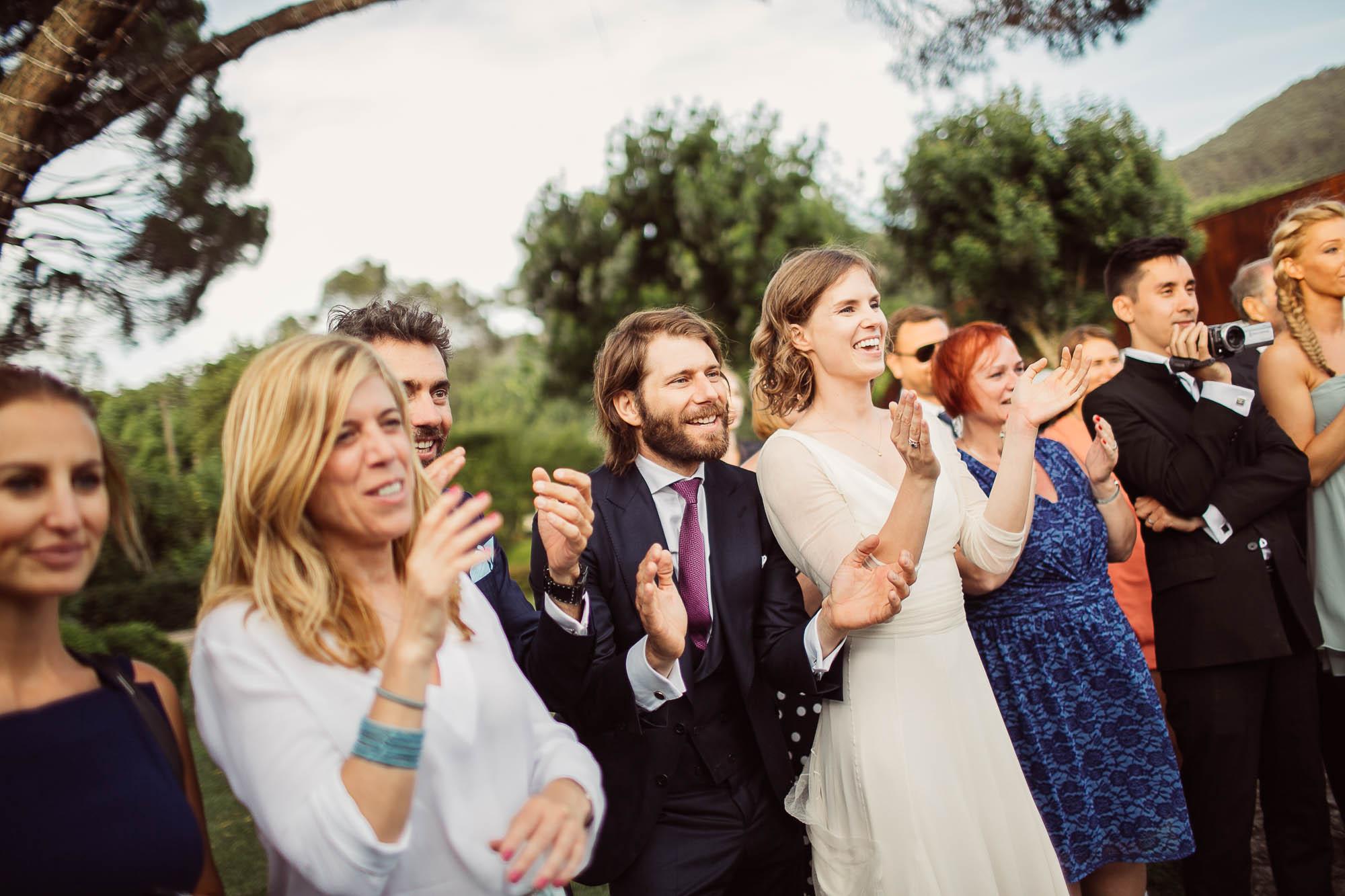 Marido y mujer junto con varios invitados observando y aplaudiendo un expectaculo del barman
