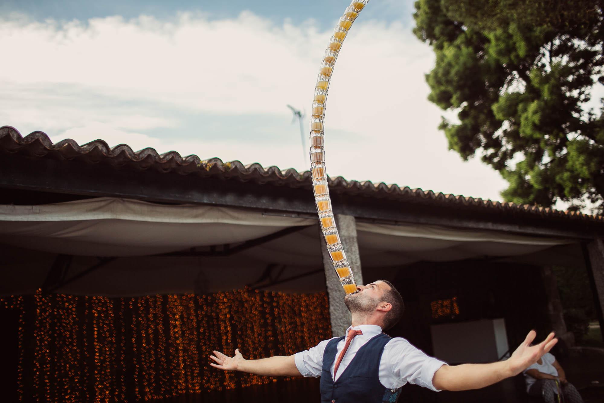 El barman haciendo equilibrio con una torre de veinte vasos sobre su boca