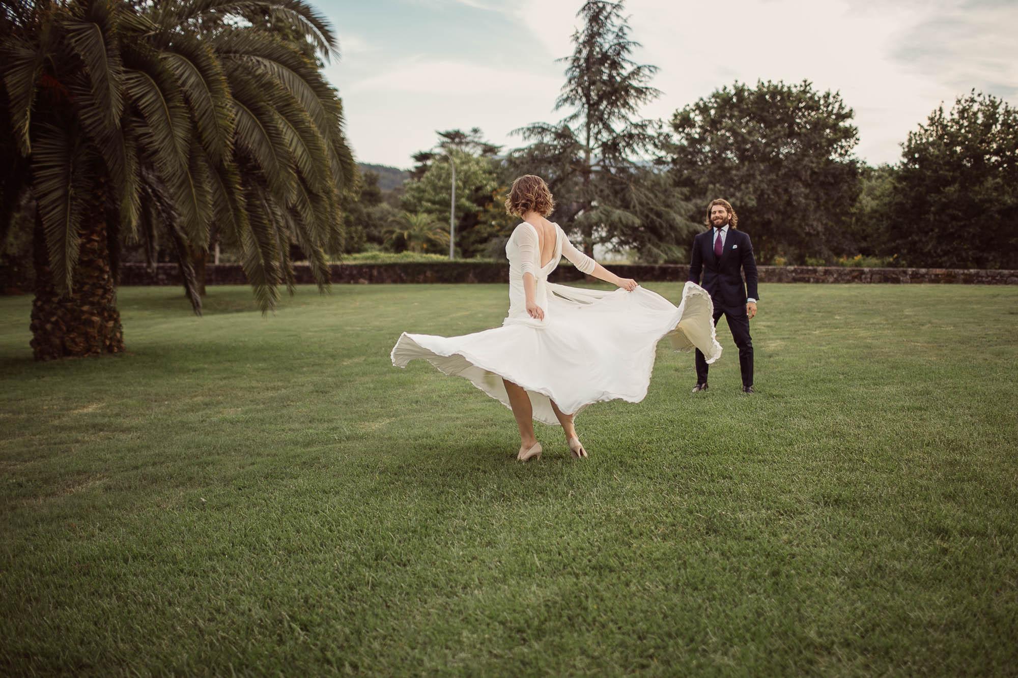 La novia ondeando la falda blanca de su vestido mientras su marido la observa