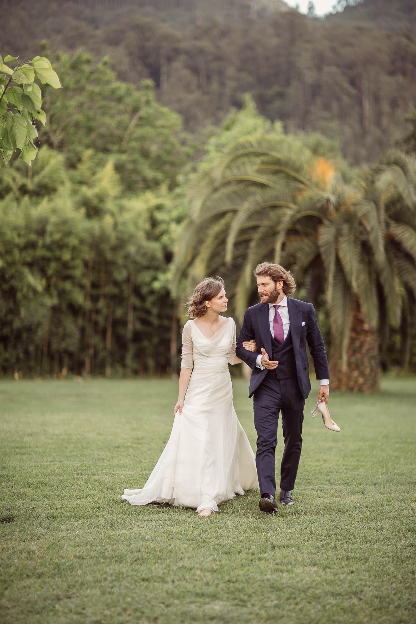 Marido y mujer caminando de vuelta al banquete mientras el marido sujeta los tacones de su mujer