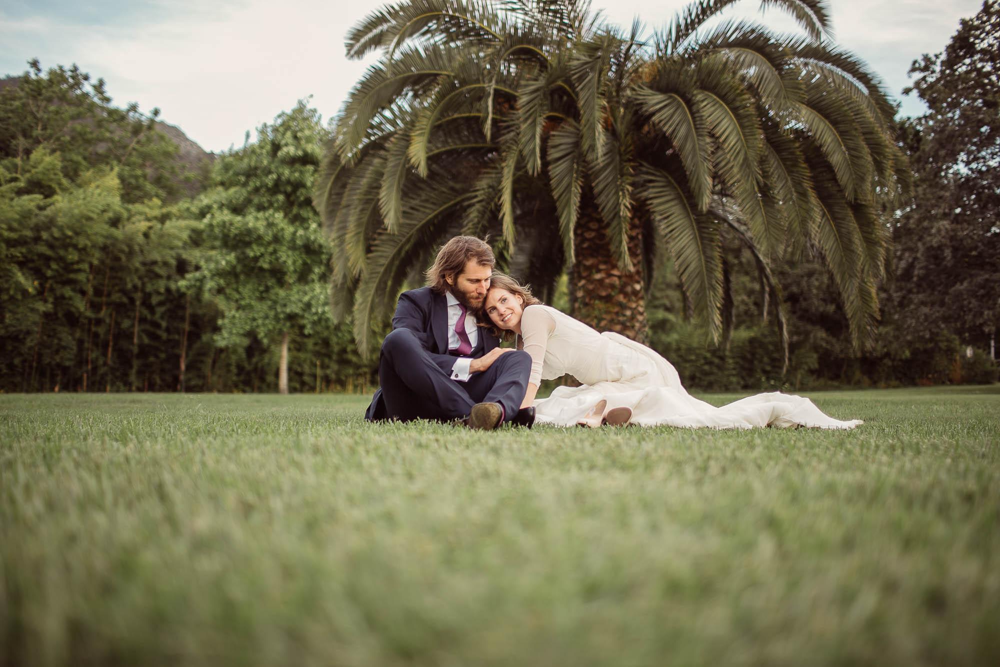 Marido y mujer senteados en el cesped de la finca mirando hacia el banquete