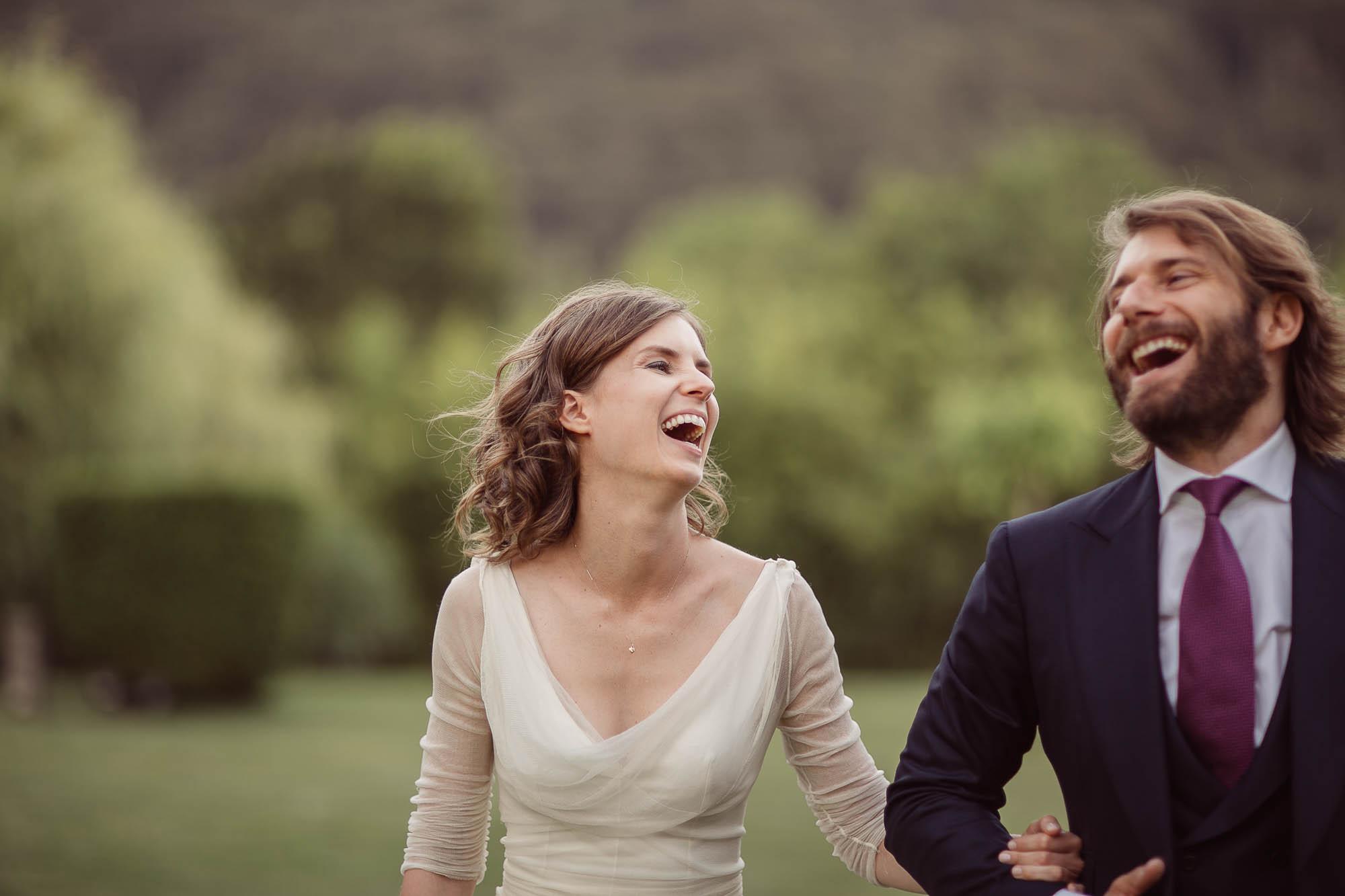 Marido y mujer riéndose mientras caminan por el jardin