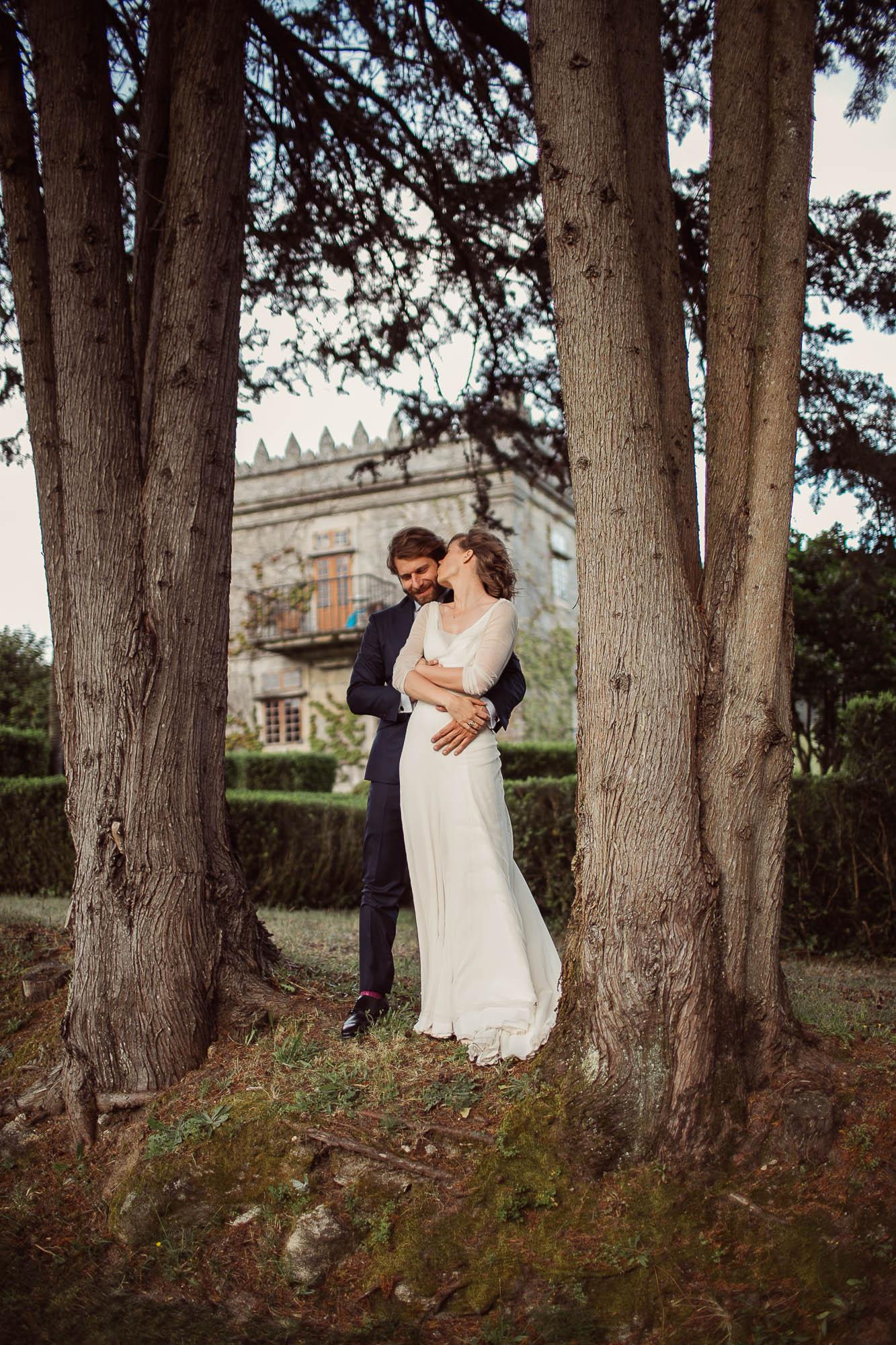 El novio abrazando a su mujer por dentras entre dos pinos mientras ella se gira para darle un beso