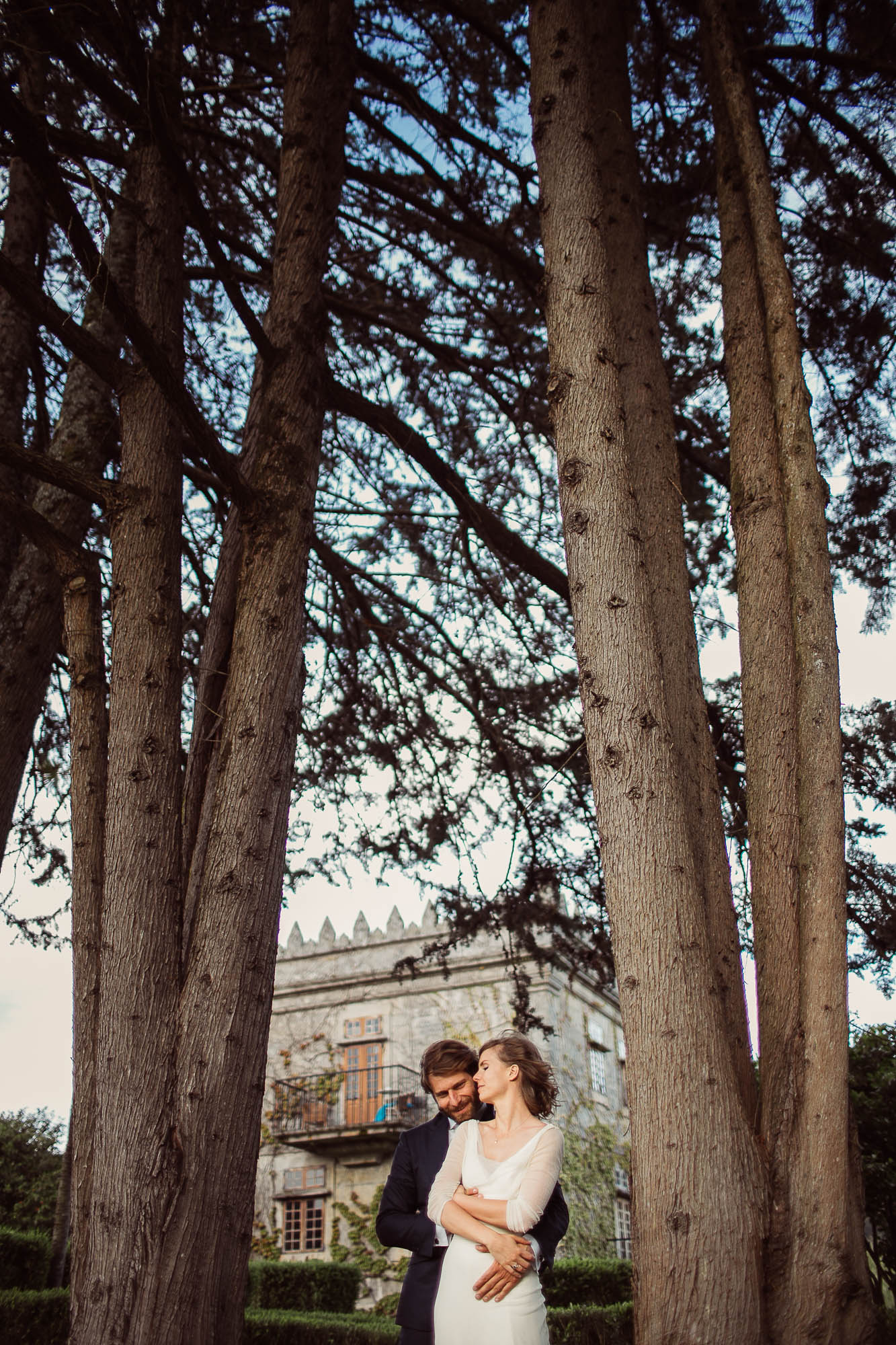 La novia se gira para verle la cara a su marido mientras éste le abraza por detrás