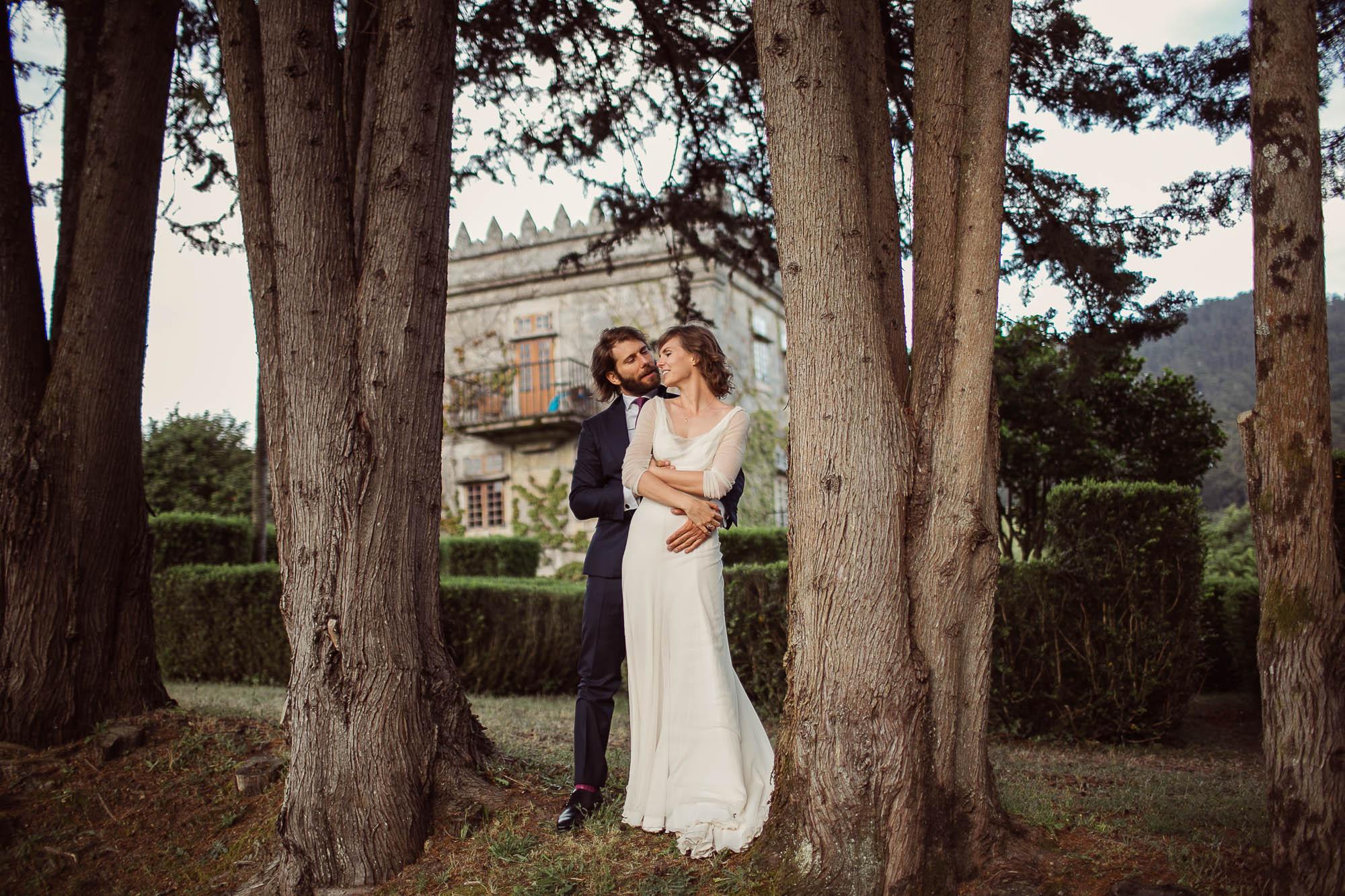 Marido y mujer mirándose a la cara mientras éste la abraza por detrás entre dos pinos el día de su boda