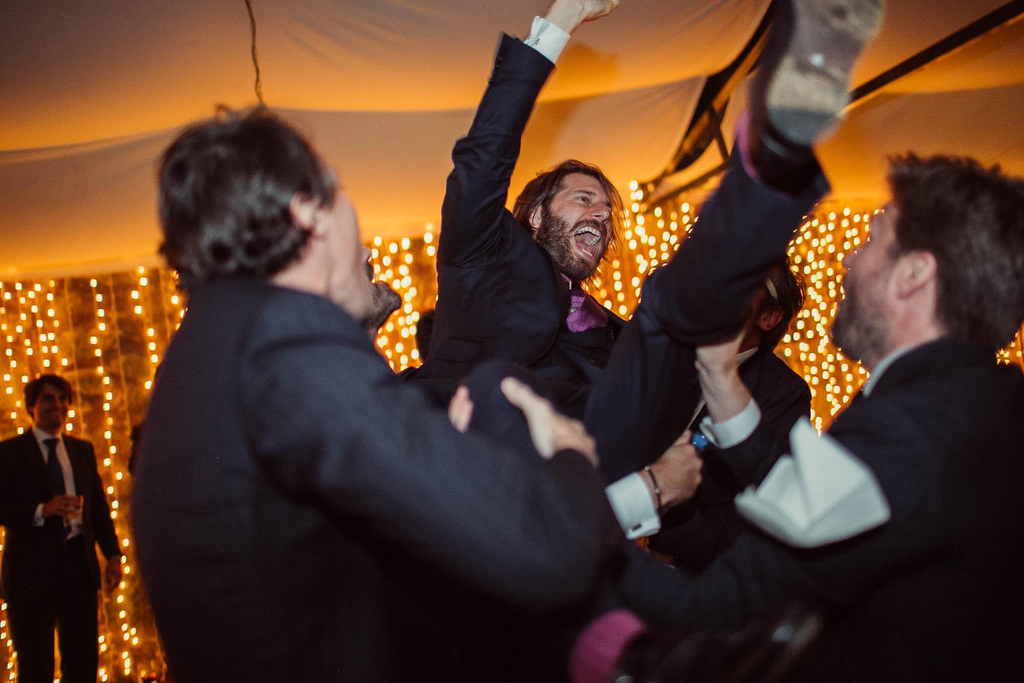 Los invitados levantando al novio por encima de los hombros entre varios emocionados durante la fiesta de la boda