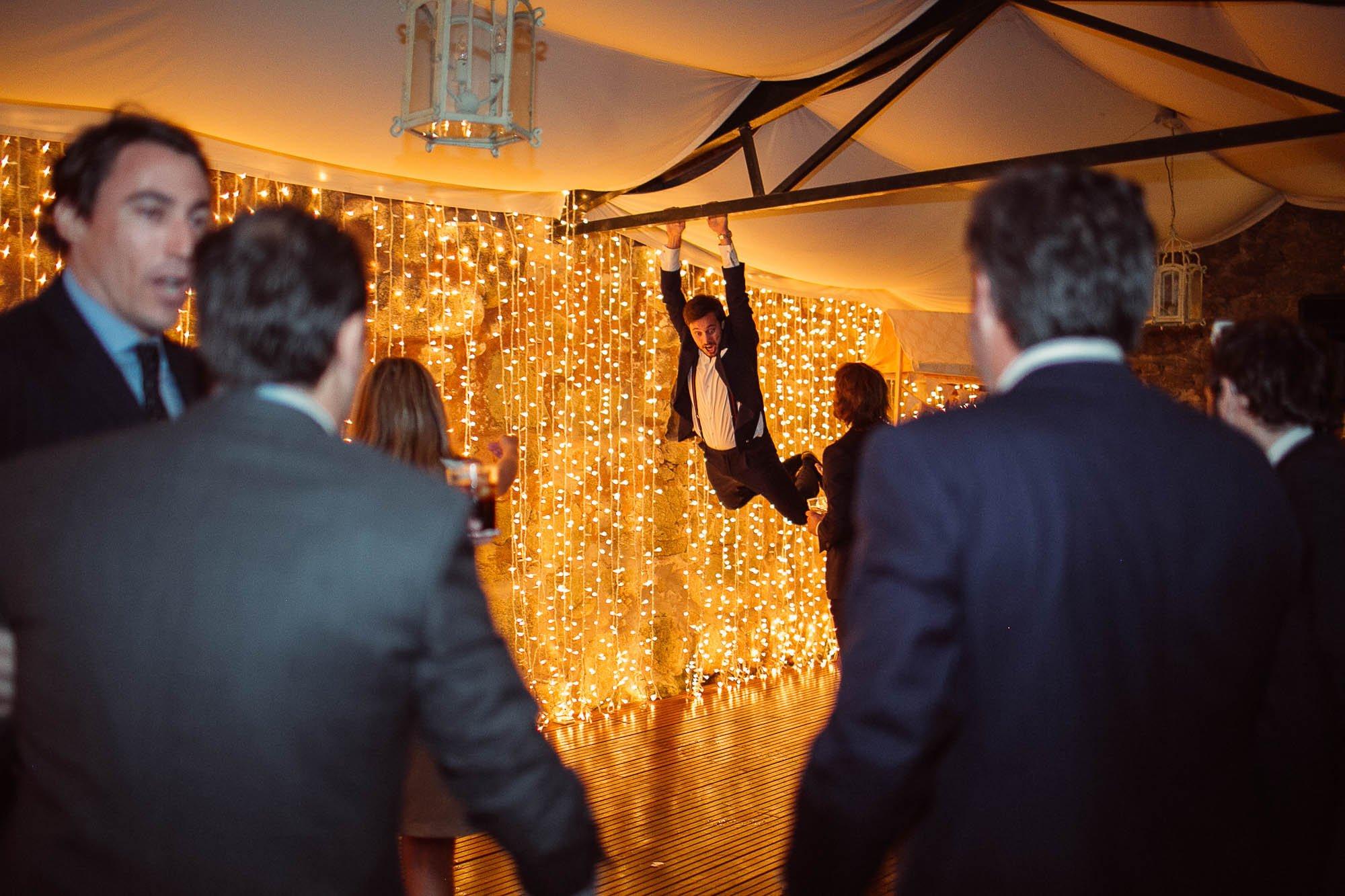 Un invitado colgado de la viga de metal que sostiene la carpa de la pista de baile durante la fiesta de la boda