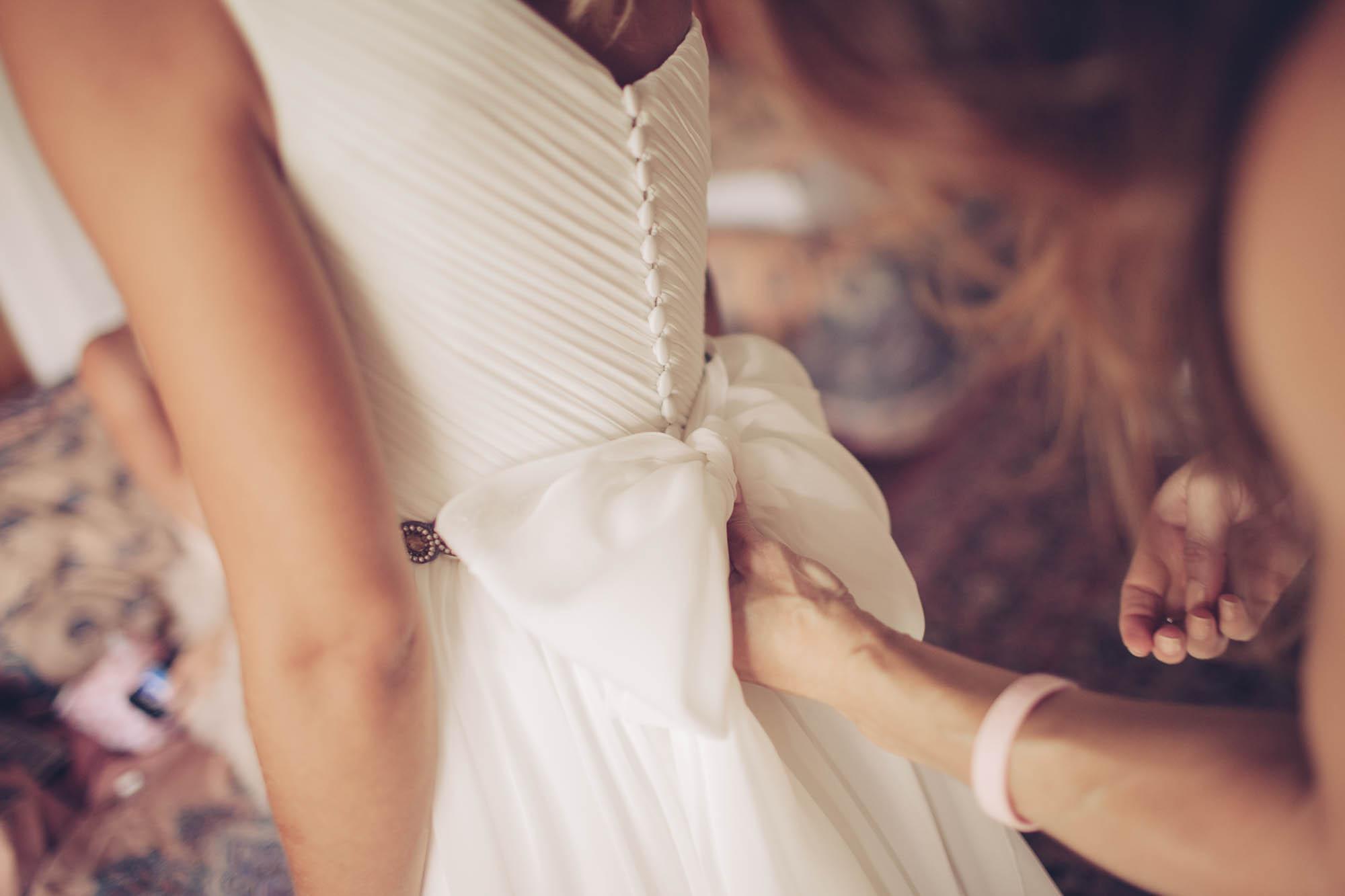 La amiga arregla el lazo de la espalda del vestido