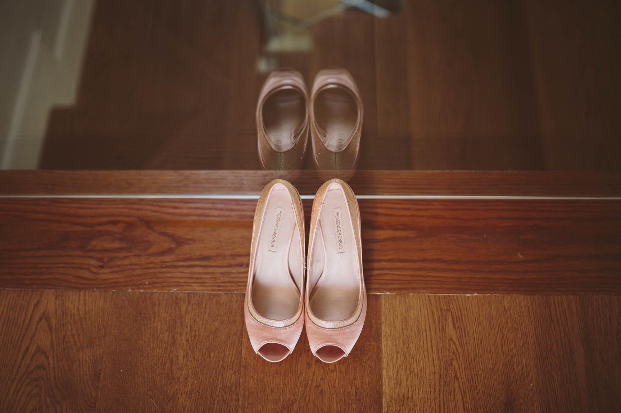 Zapatos de terciopelo rosa reflejados en un cristal