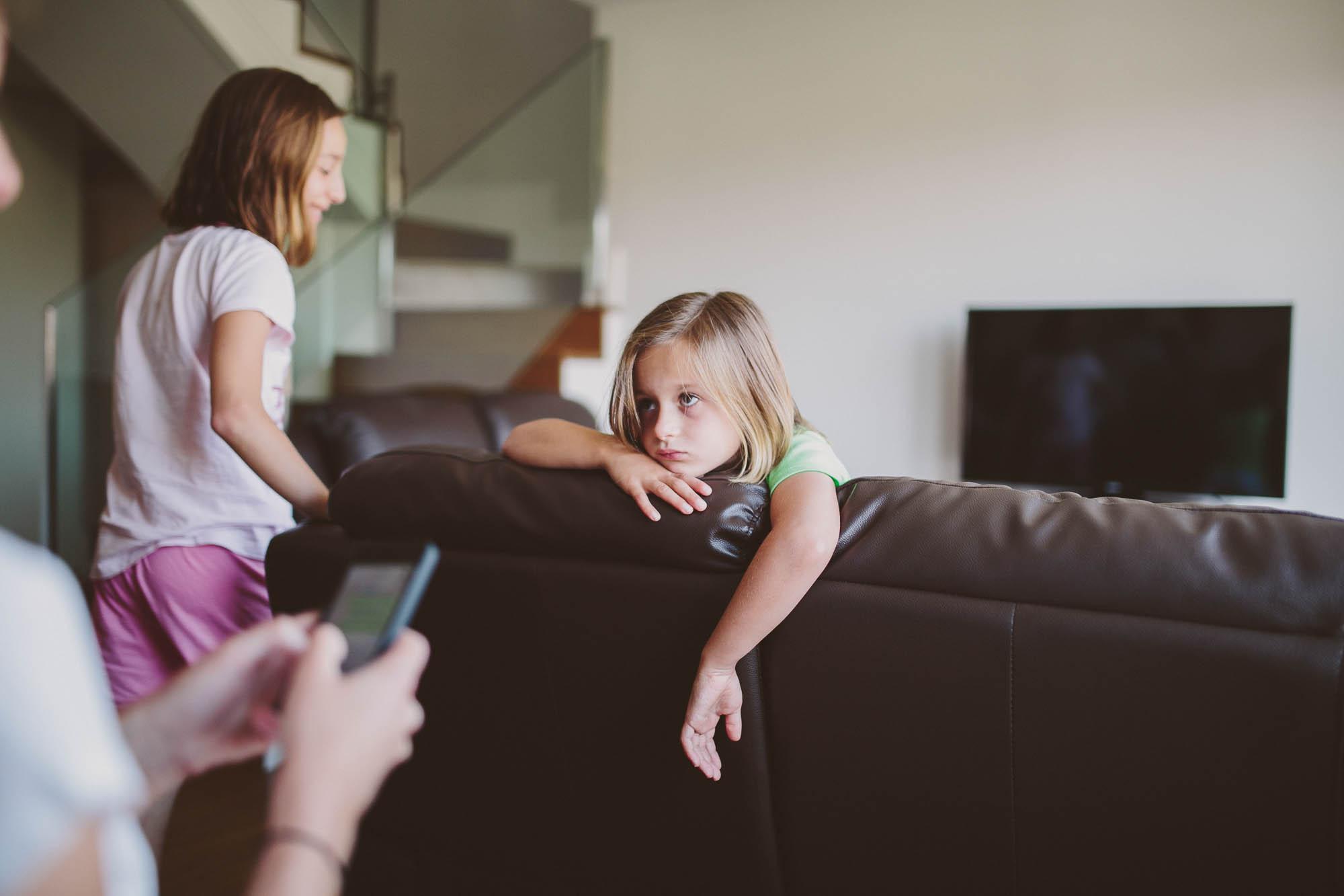 Una niña sentada en el sofá con gesto aburrido y la familia espera a la novia