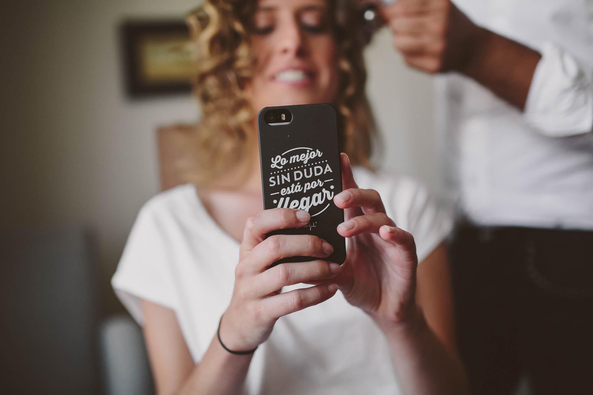 La novia mira su móvil mientras la peinan