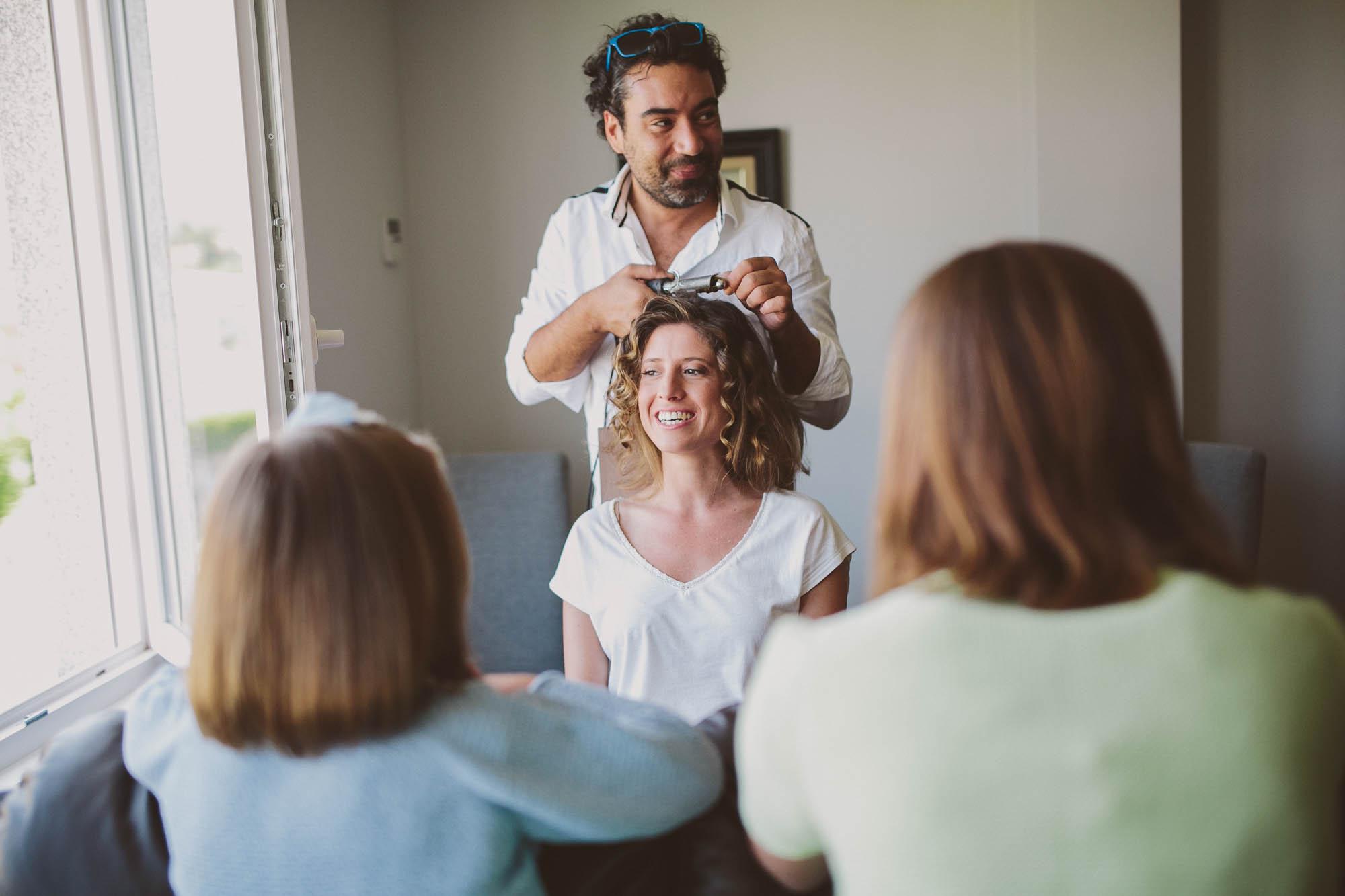 la novia sonriente con su familia mientras le hacen el peinado