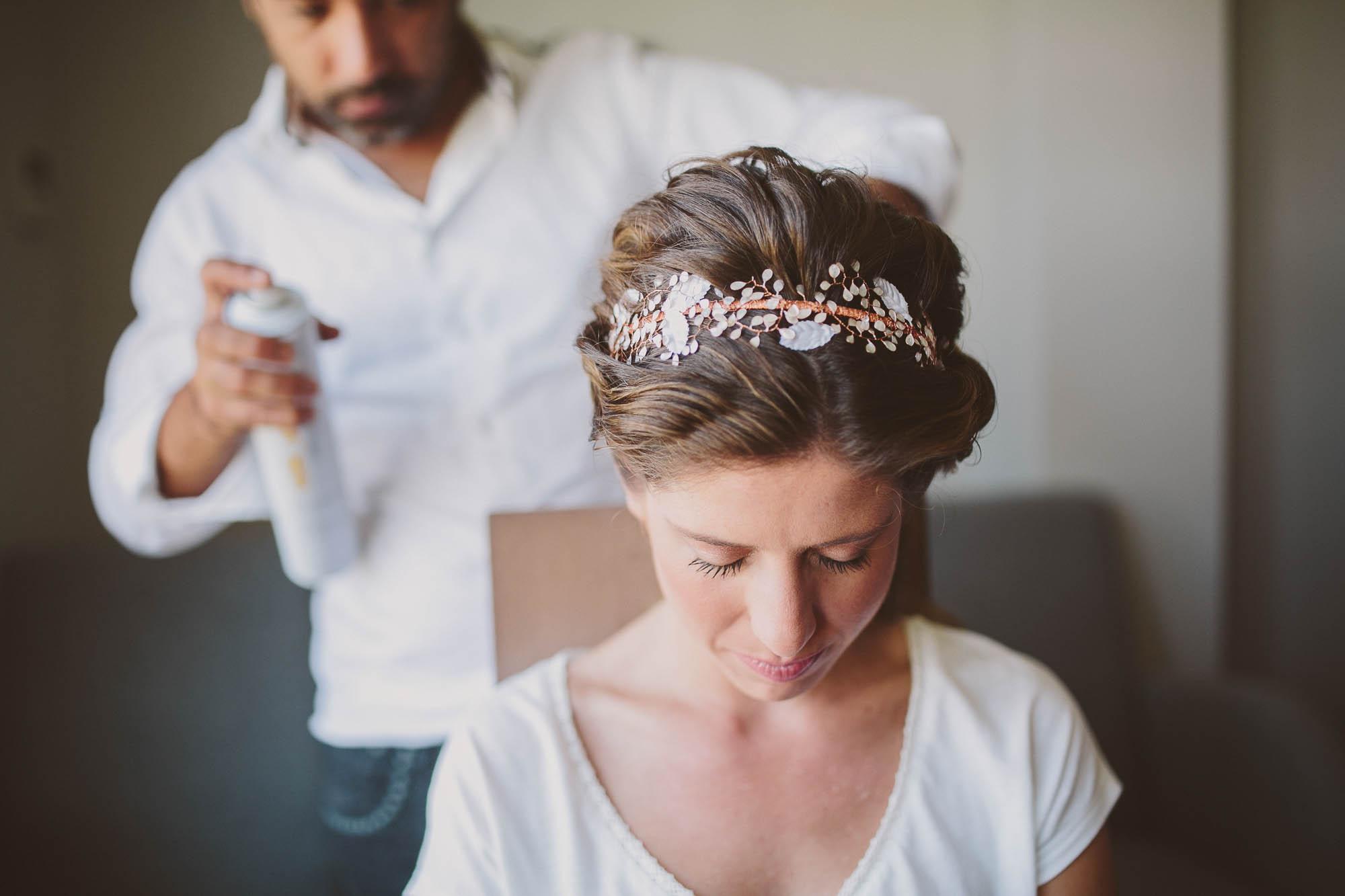 El peluquero rocía de laca el peinado final con un tocado de flores