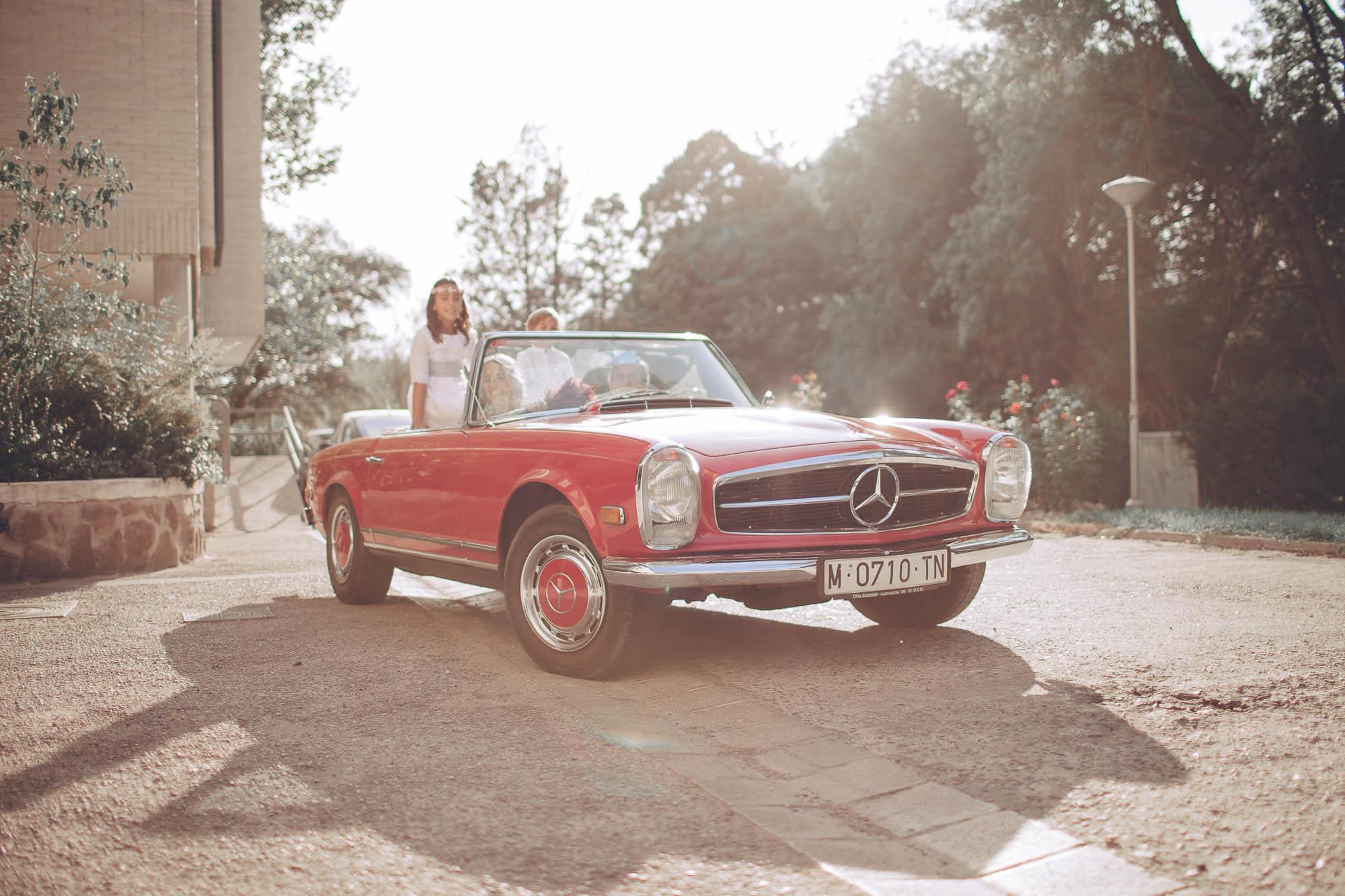 Los niños pasean env el coche antiguo rojo