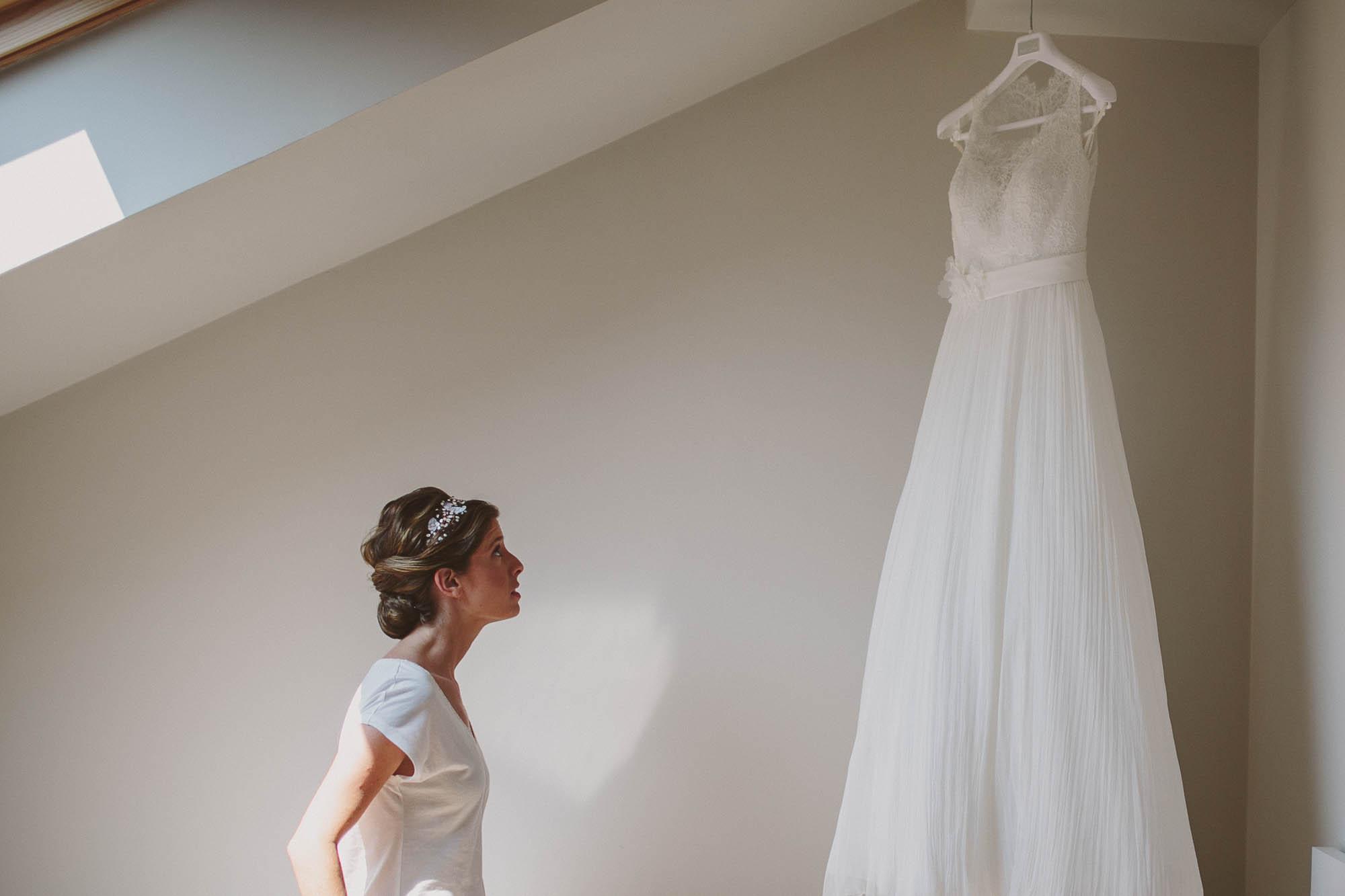 La novia casi lista mira su vestido para la boda