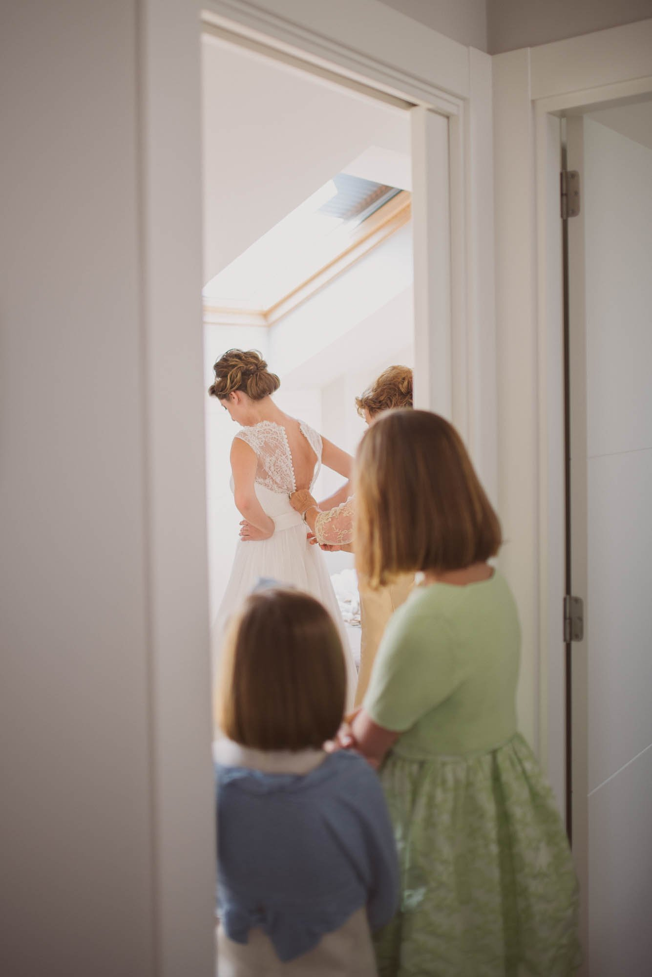 La madre ayuda a la novia a ponerse el vestido mientras las niñas la miran