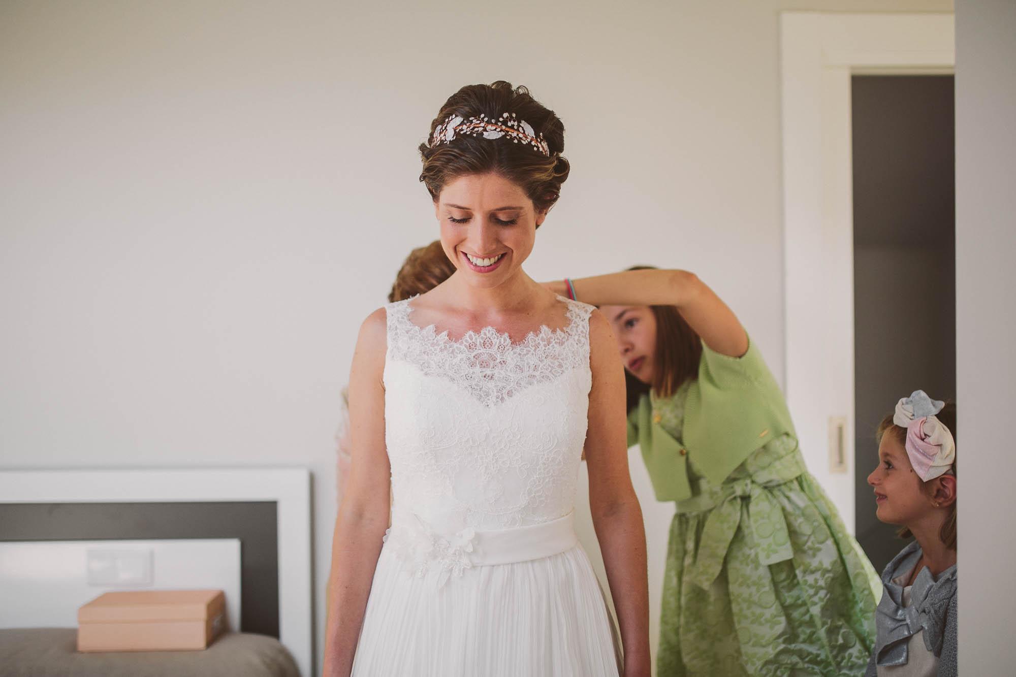 La novia sonríe mientras las niñas y la madre le cierran el vestido