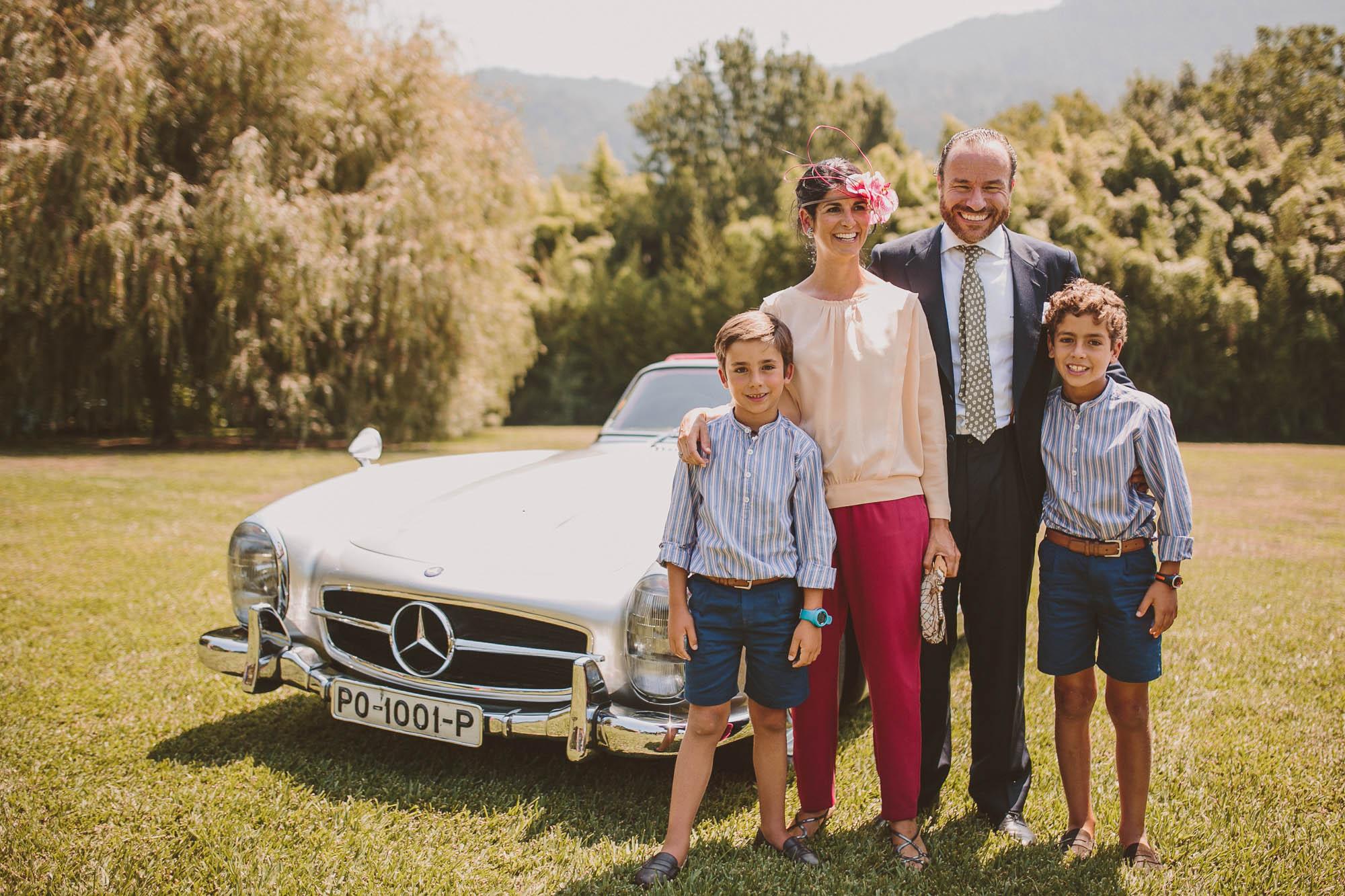 La familia posa sonriente delante dle coche en el jardín