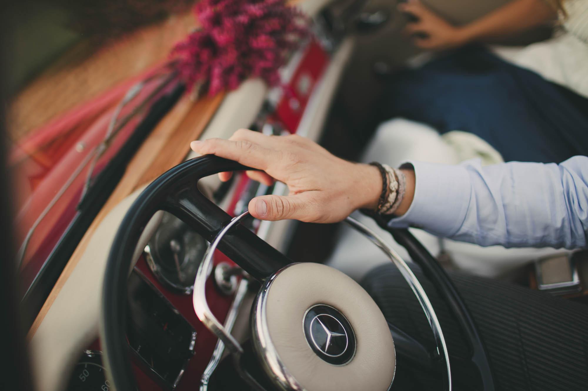 El novio sujeta el volante del coche de bodas
