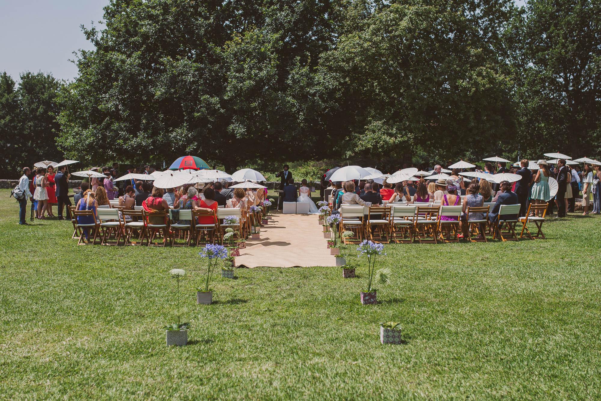 Los invitados en la ceremonia cubiertos con sombrillas en el jardín