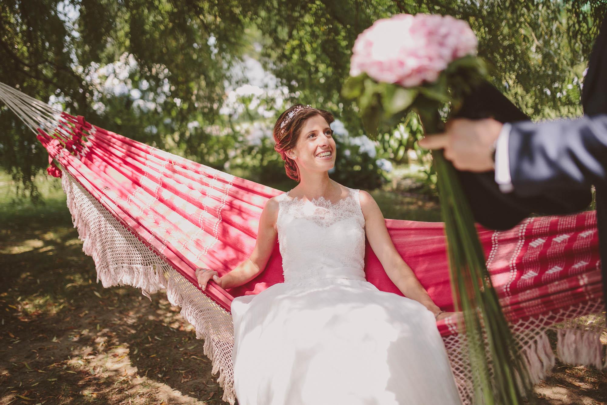 La novia sentada en la hamaca  mira sonriente al novio que sostiene su ramo