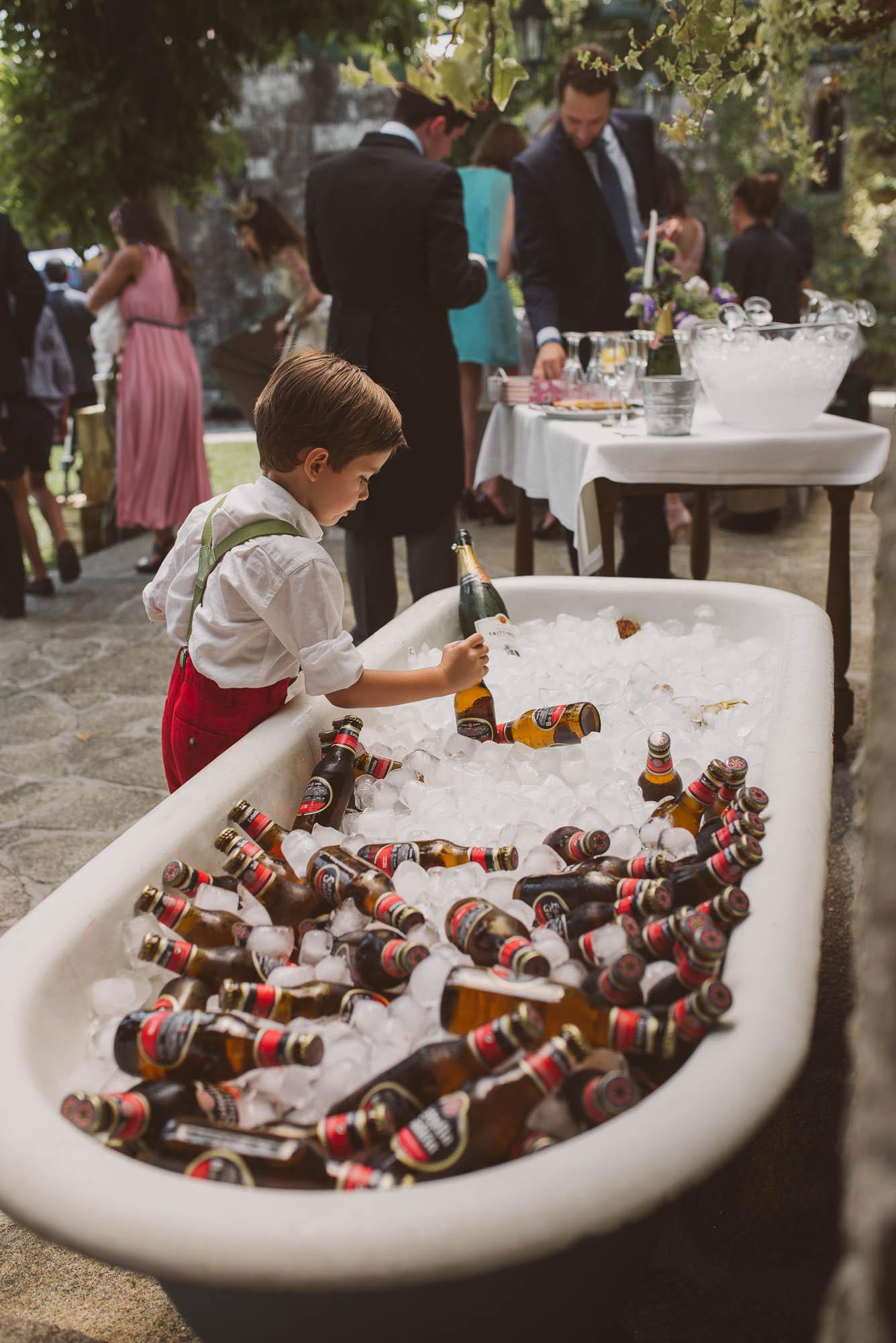 Un niño coge una cerveza de la bañera durante el cóctel de la boda