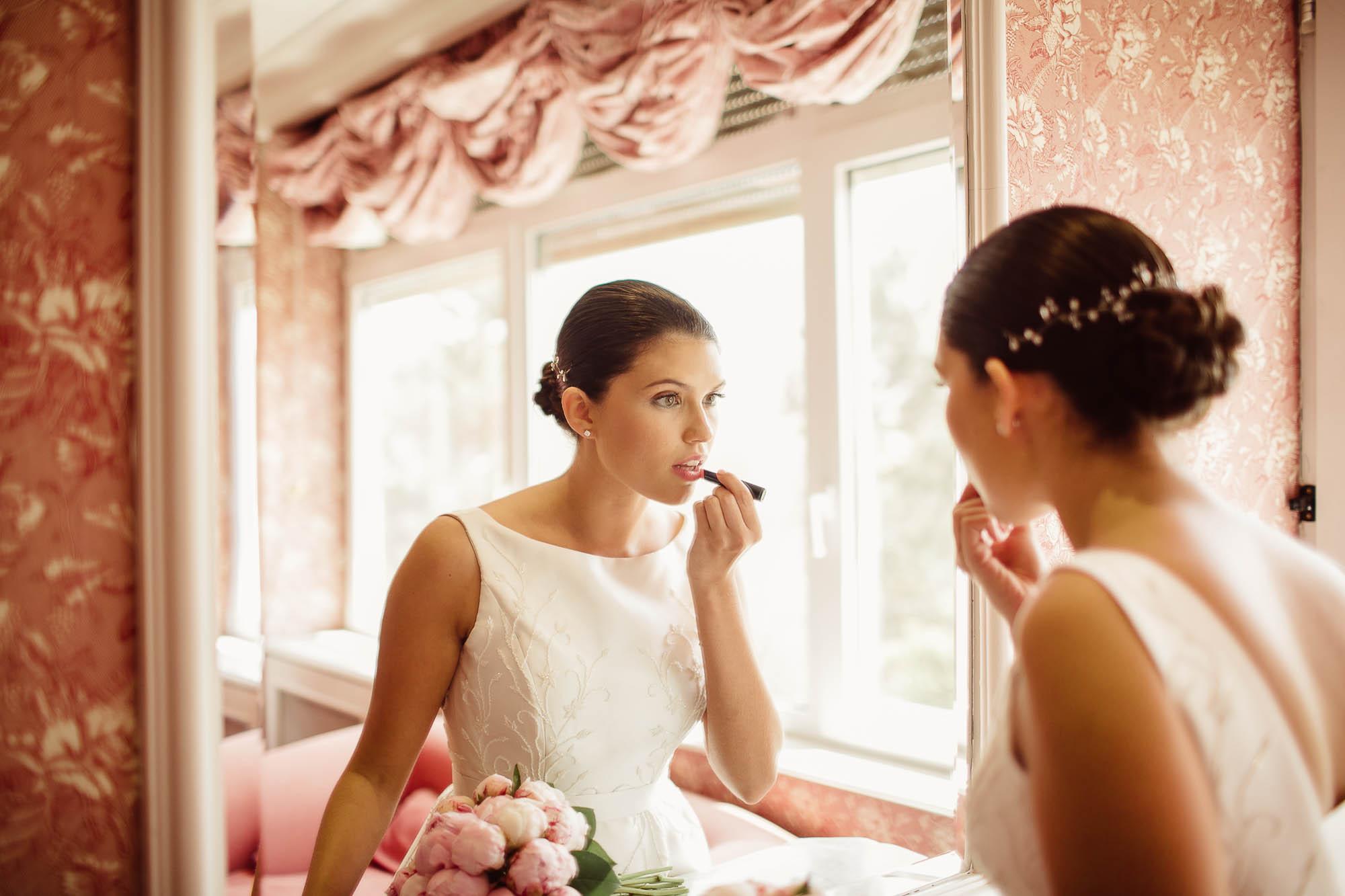 Una novia arreglándose en el espejo el día de su boda