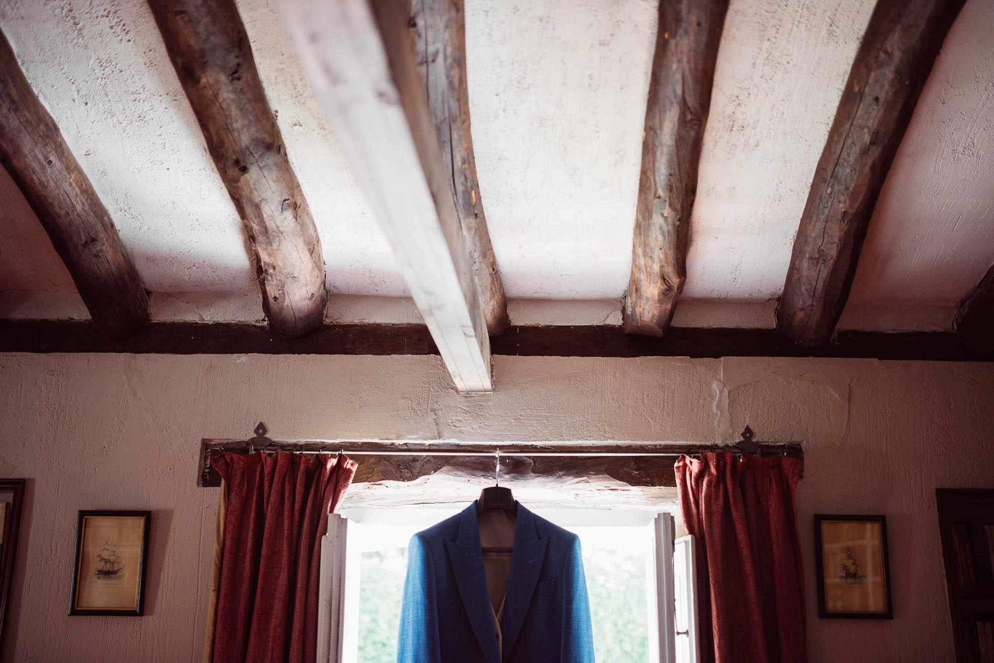 La chaqueta azul del novio colgada de la ventana en la casa rural durante los preparativos