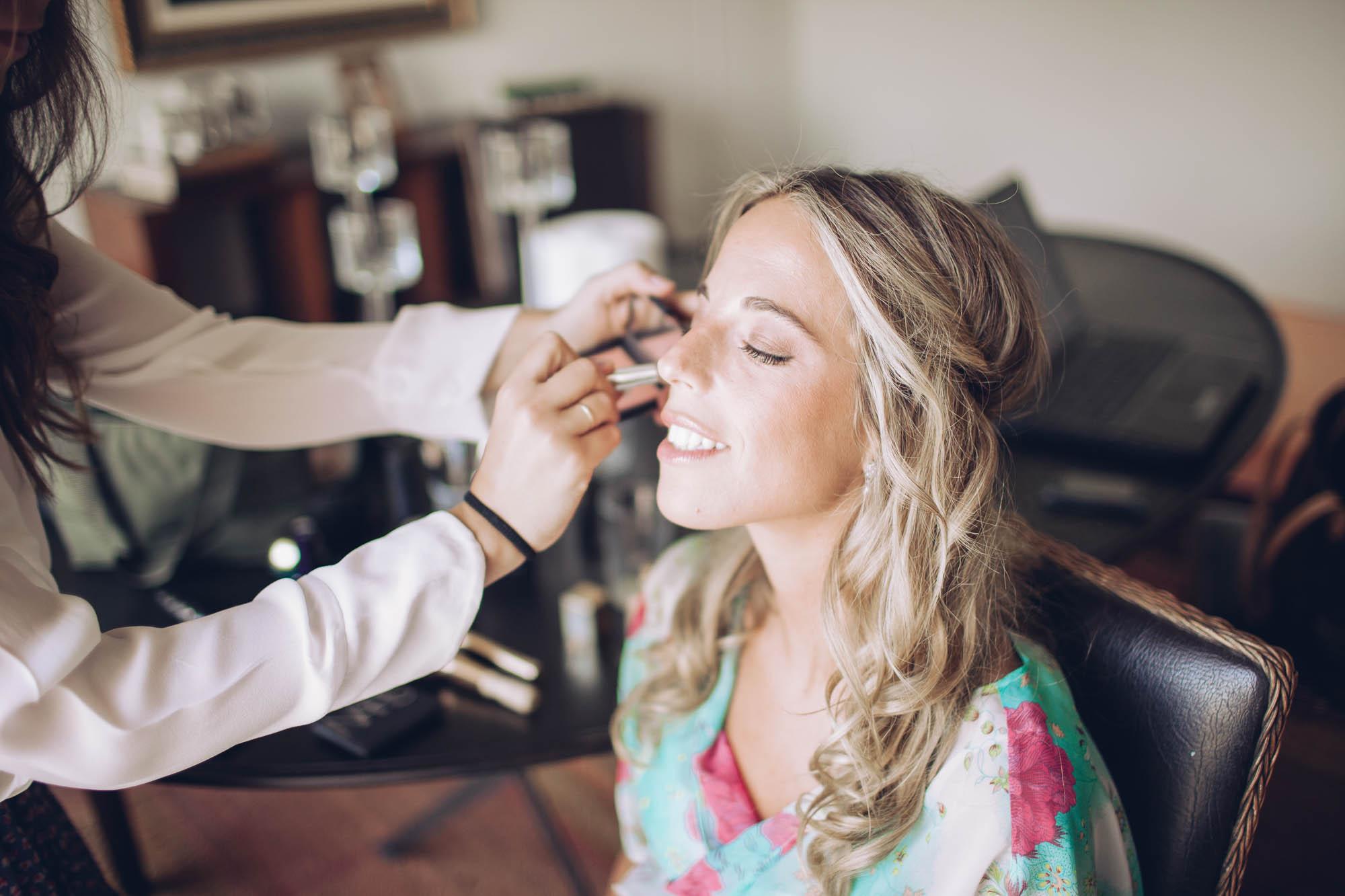Novia feliz maquillándose para la boda