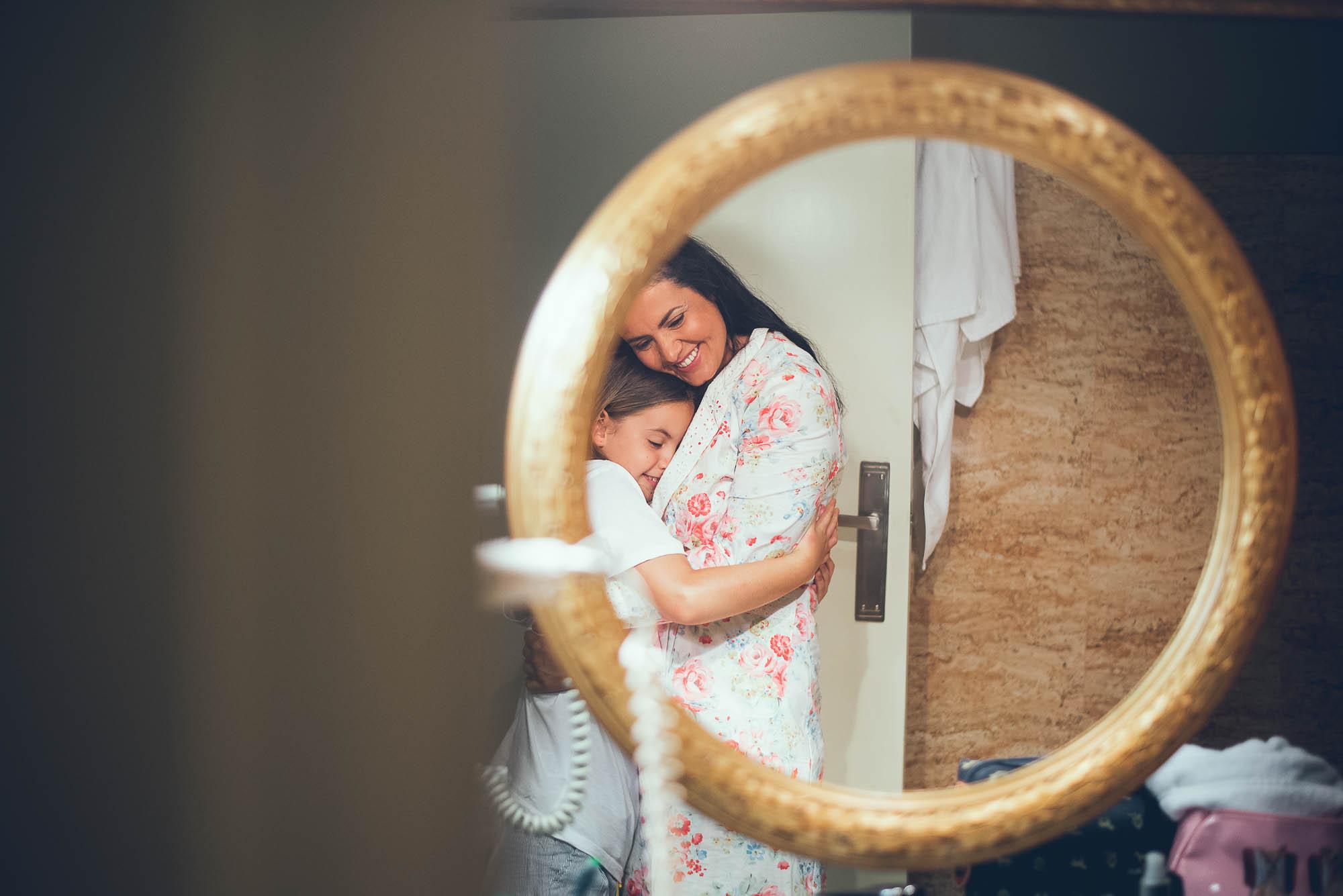 El reflejo en un espejo de una novia abrazando a su hermana pequeña