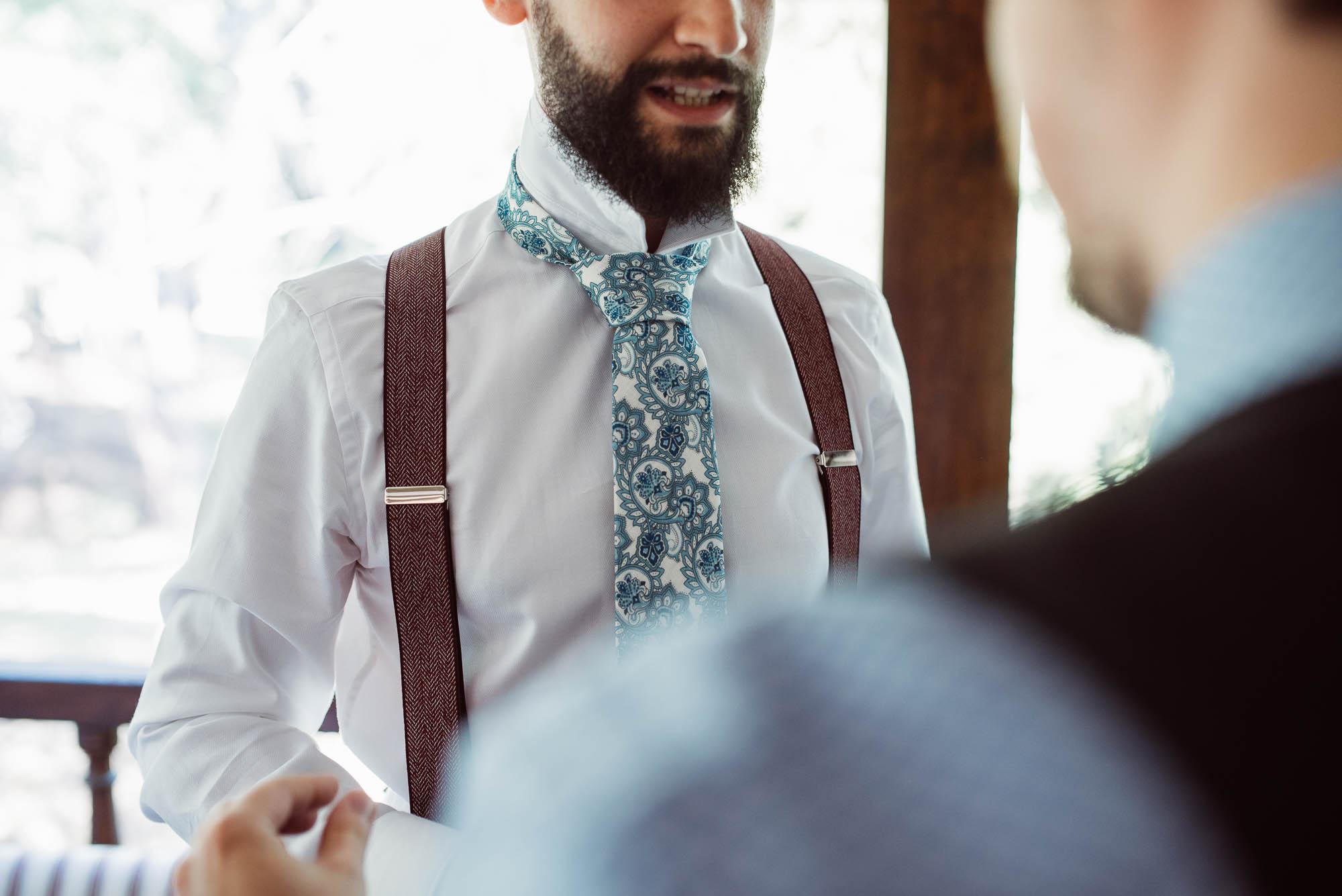 El novio con la corbata azul durante los preparativos