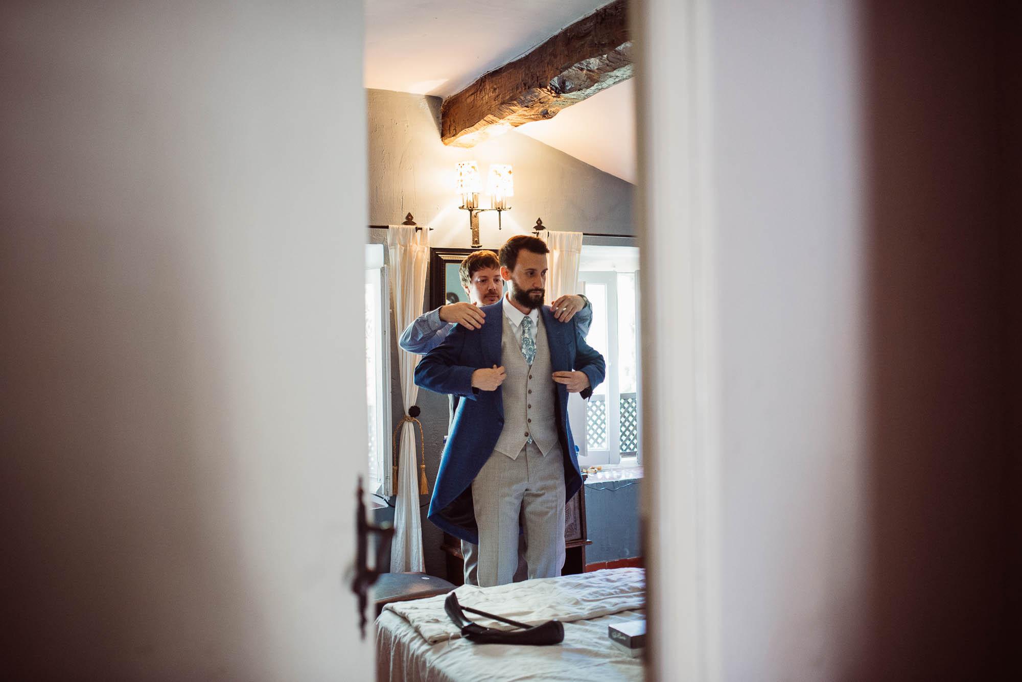 El novio vistiéndose con su hermano el día de la boda