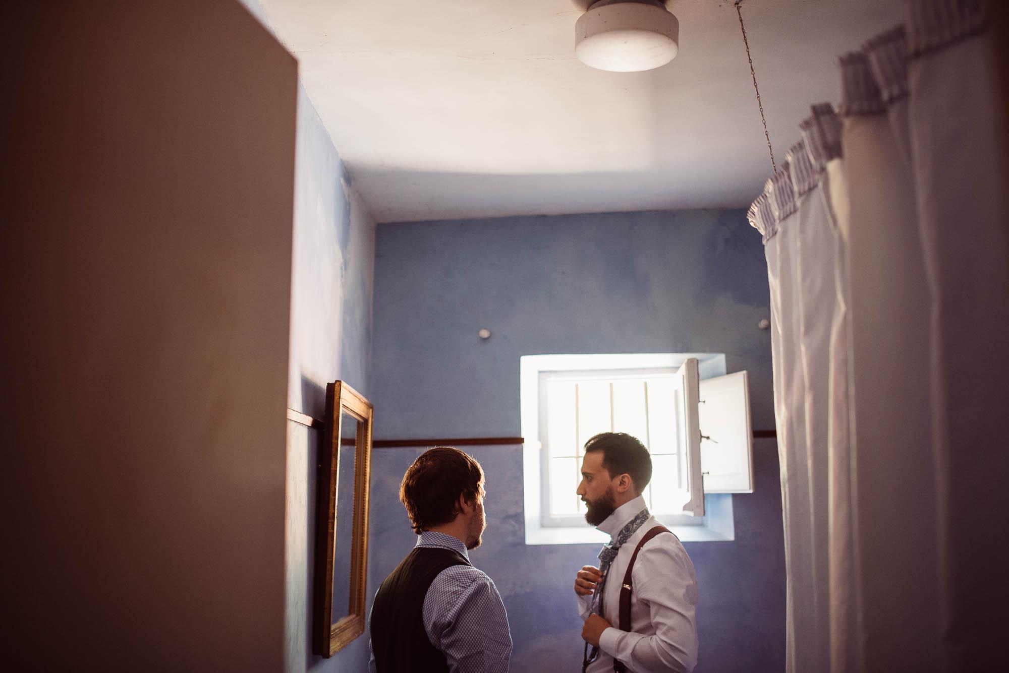 El novio se coloca la corbata frente al espejo durante los preparativos