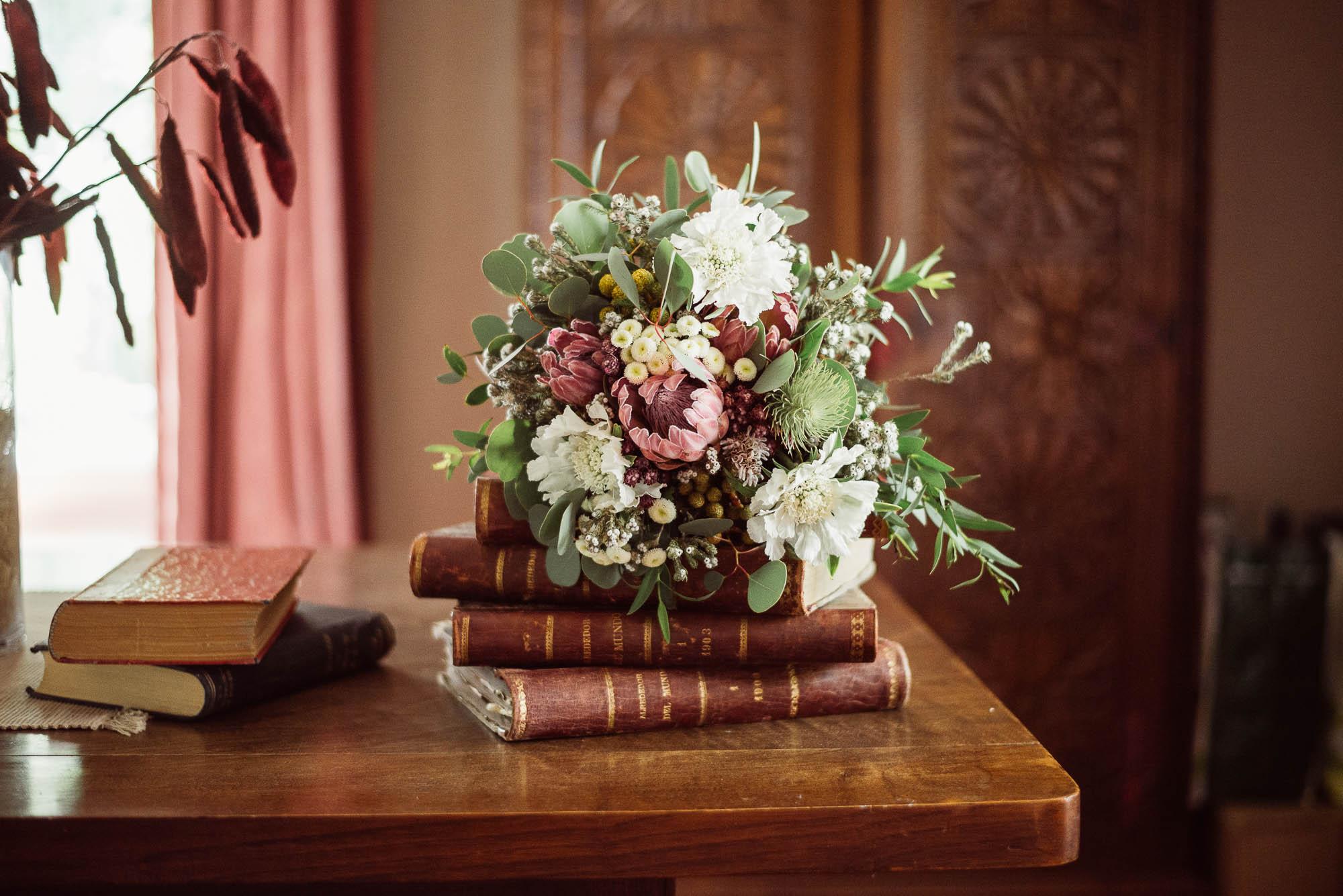 El ramo de la novia sobre libros en la biblioteca