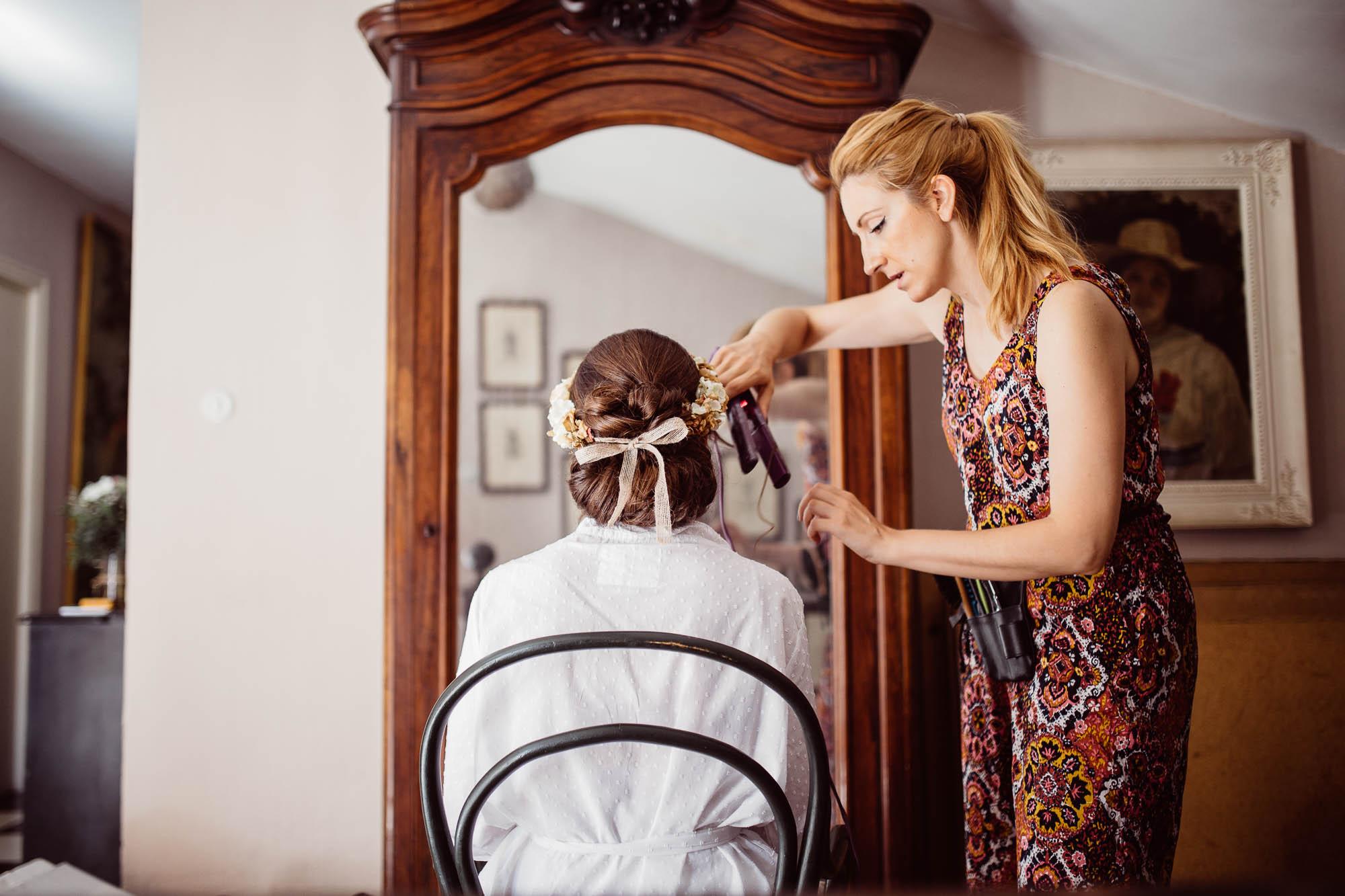 La peluquera peina a la novia durante los preparativos