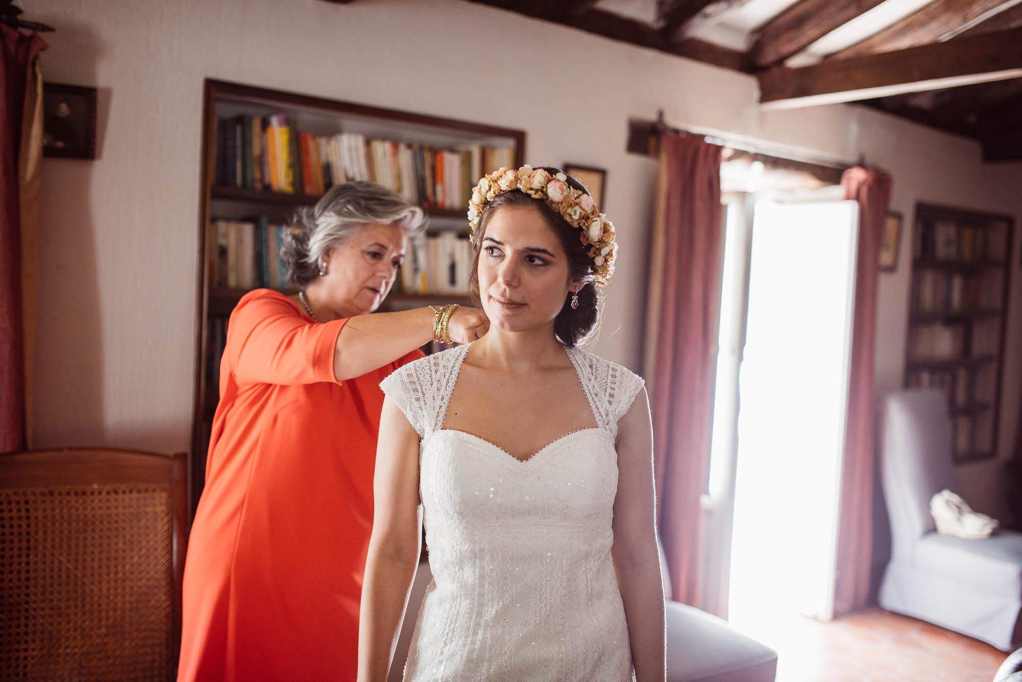 La madre ayuda a la novia a ponerse el vestido