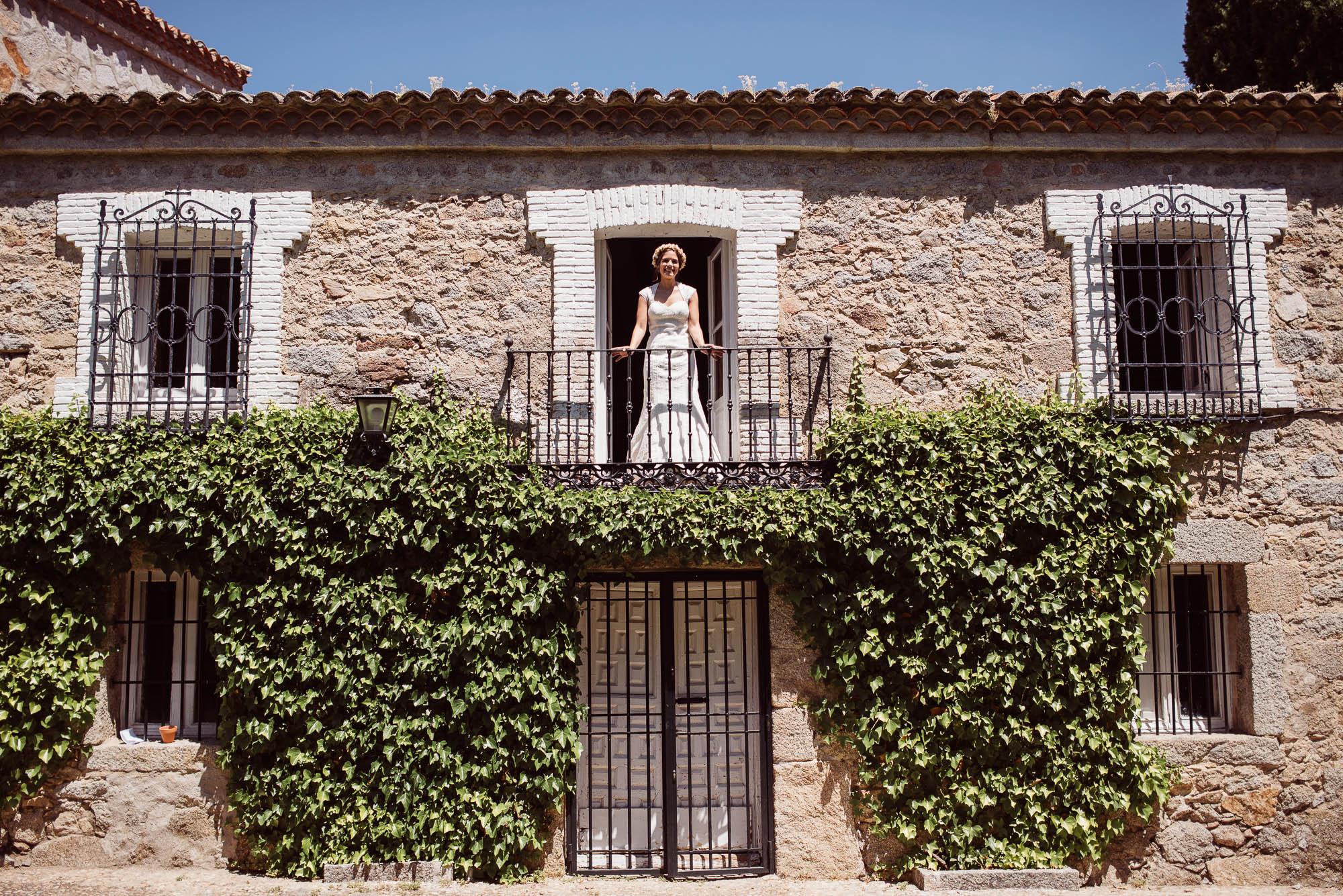 La novia sale al balcón de la casa rural para saludar a los invitados