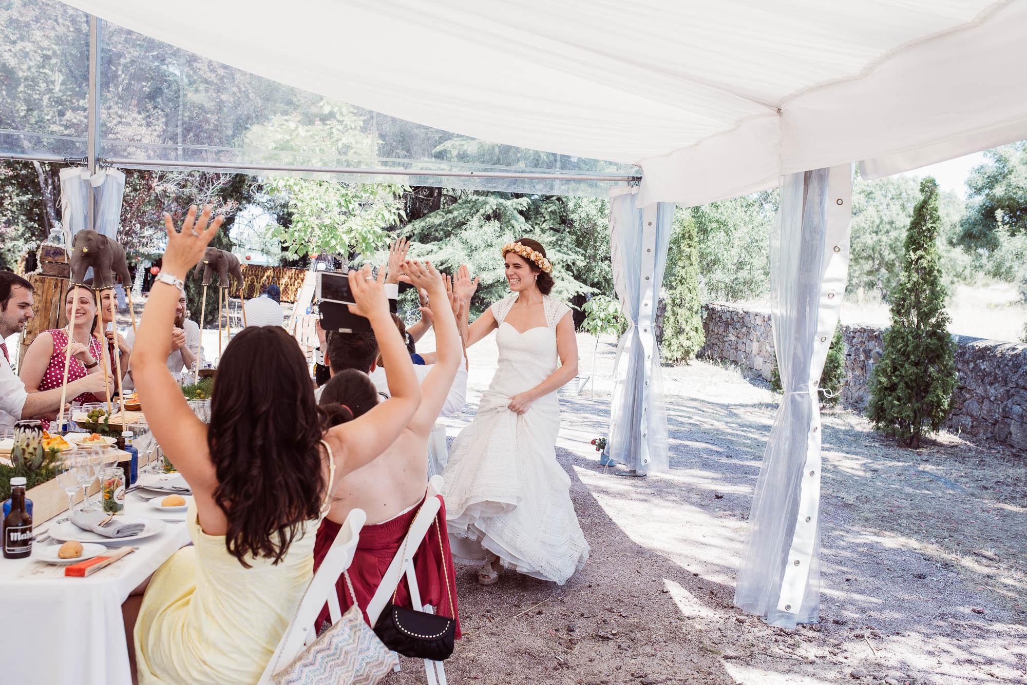 La novia llega al comedor saludando a los invitados