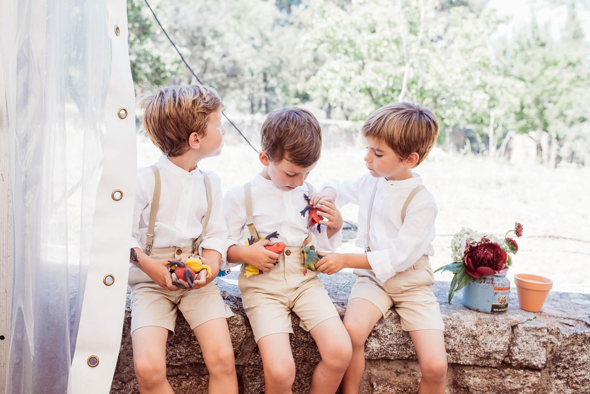 Tres niño que juegan con sapos de colores durante la comida