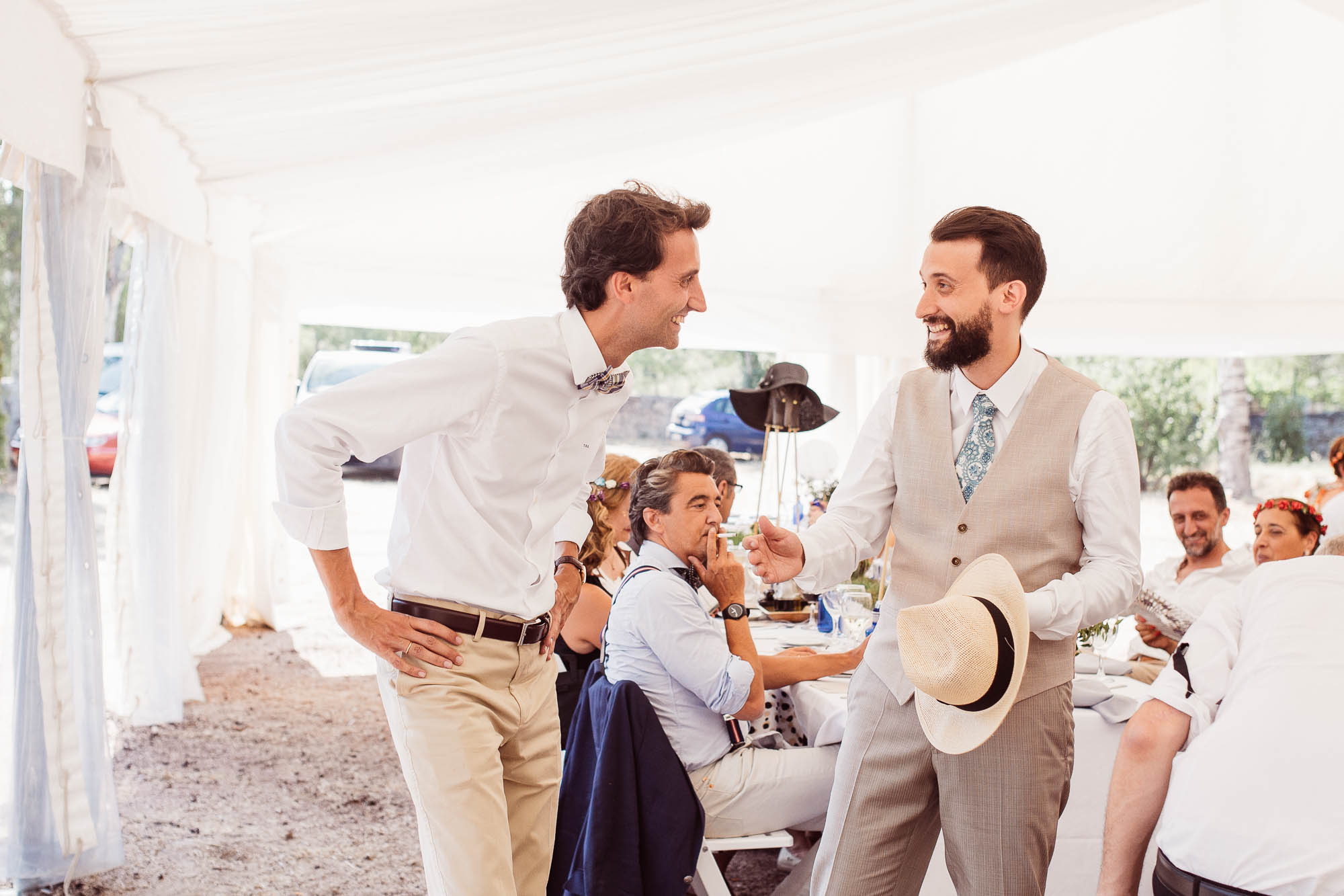 El novio charla con un invitado durante la comida de la boda