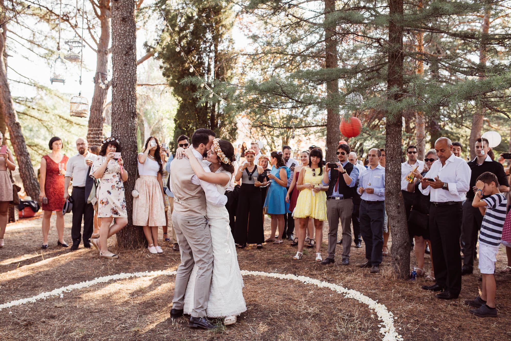 Los novios bailan abrazados rodeados por los invitados