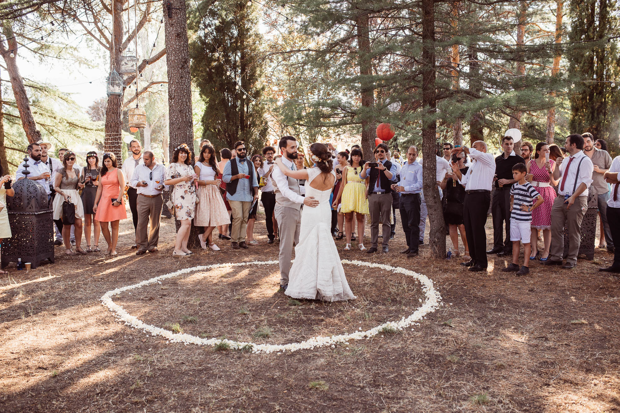Los invitados rodean a los novios que bailan en un círculo en medio del bosque