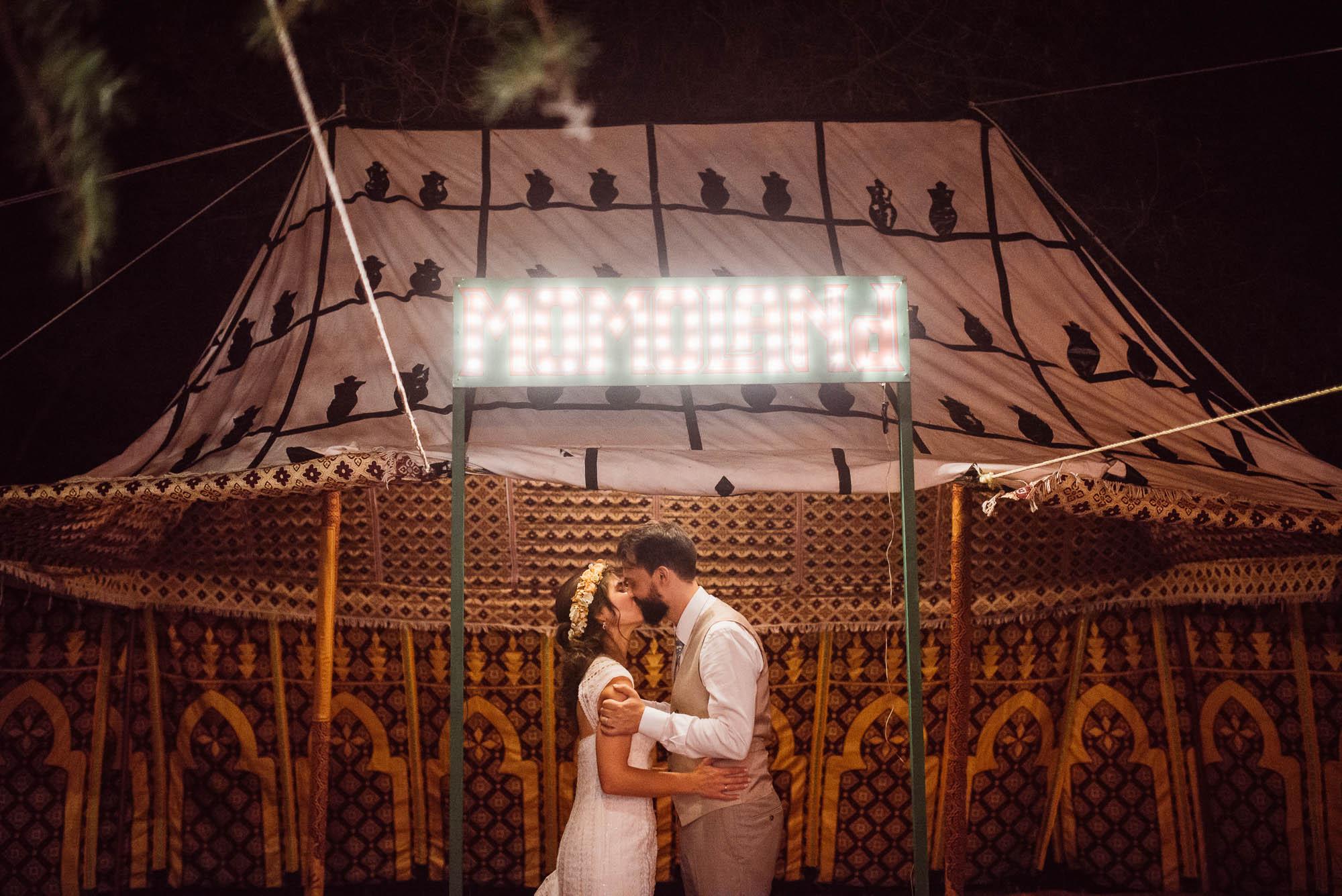 Los novios se besan al final de la fiesta bajo el cartel de Momoland