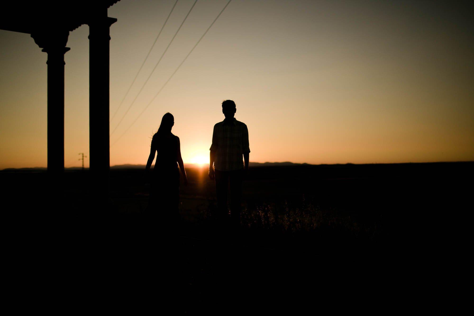 Una pareja pasea en el atardecer naranja