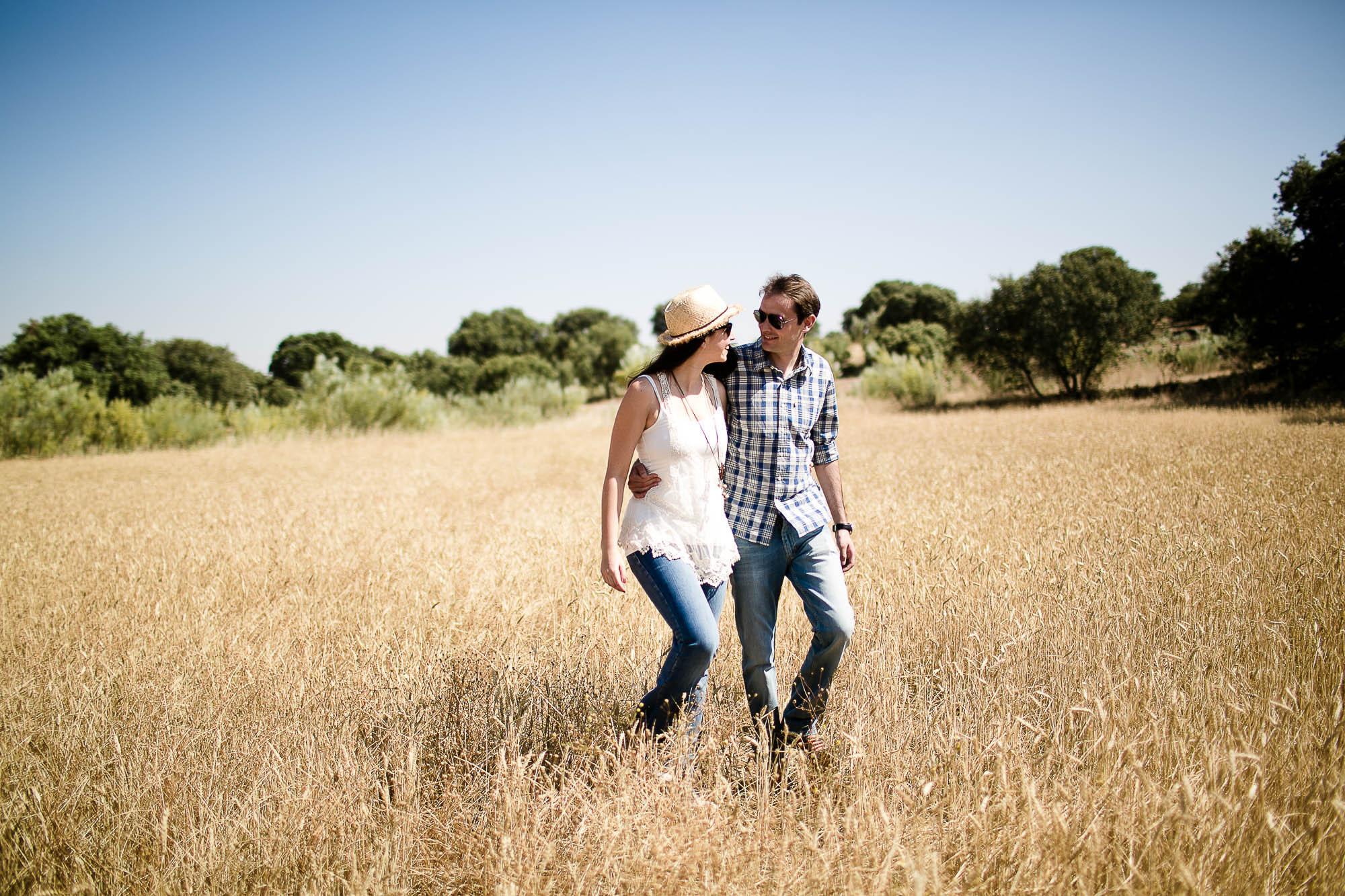 La pareja pasea abrazada por un trigal mientras se miran a los ojos